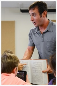 Brandon Galford takes an engaged and interactive approach as the Hebrew teacher at G.O.D. Elementary. Here, he is showing the children that Hebrew reads right to left, rather than left to right.