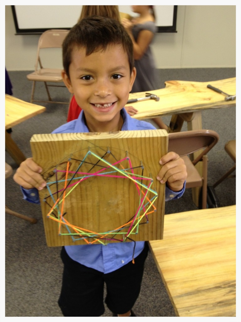 """In """"Building Fundamentals"""" class, students practiced using a hammer and nails to complete a project that introduced basic geometry, mathematics, and design."""