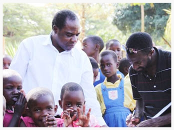 In the summer of 2011, Nyago John took his first trip back to Uganda since moving to the US in 2008. Here, he re-visits the elementary school where he attended, signing the guestbook and greeting the headmaster and children.