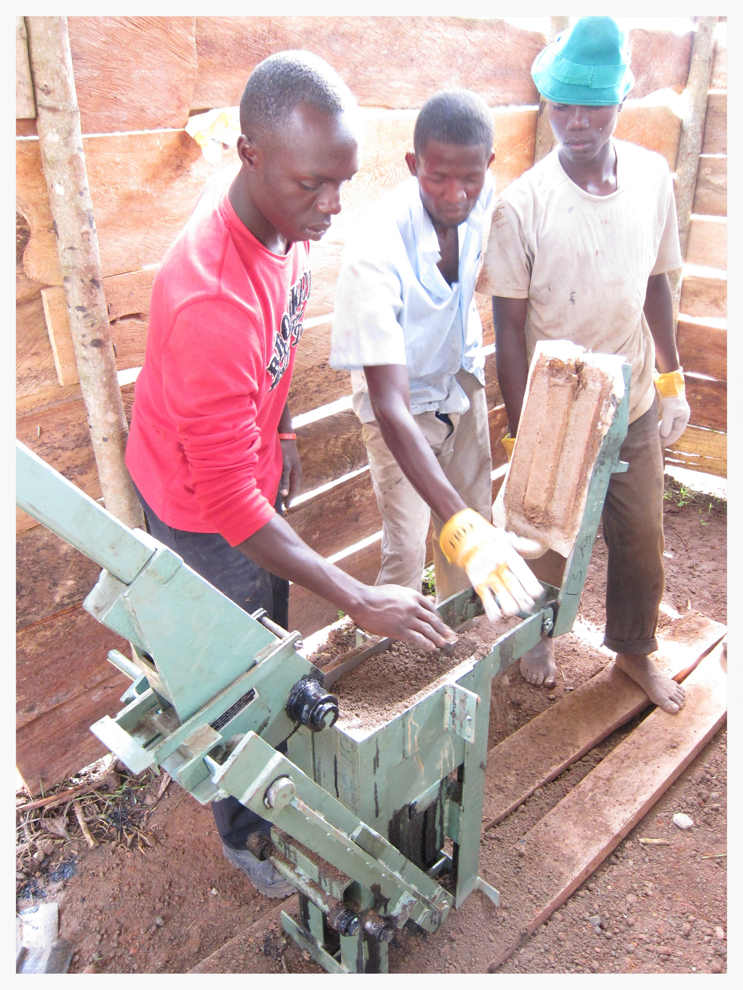 Henry, Tom and Sam (l-r) were once just dear friends of ours. Now they are helping us develop our property on a daily basis as employees. Here, they fill the Compressed Earth Block brick press with filtered soil.