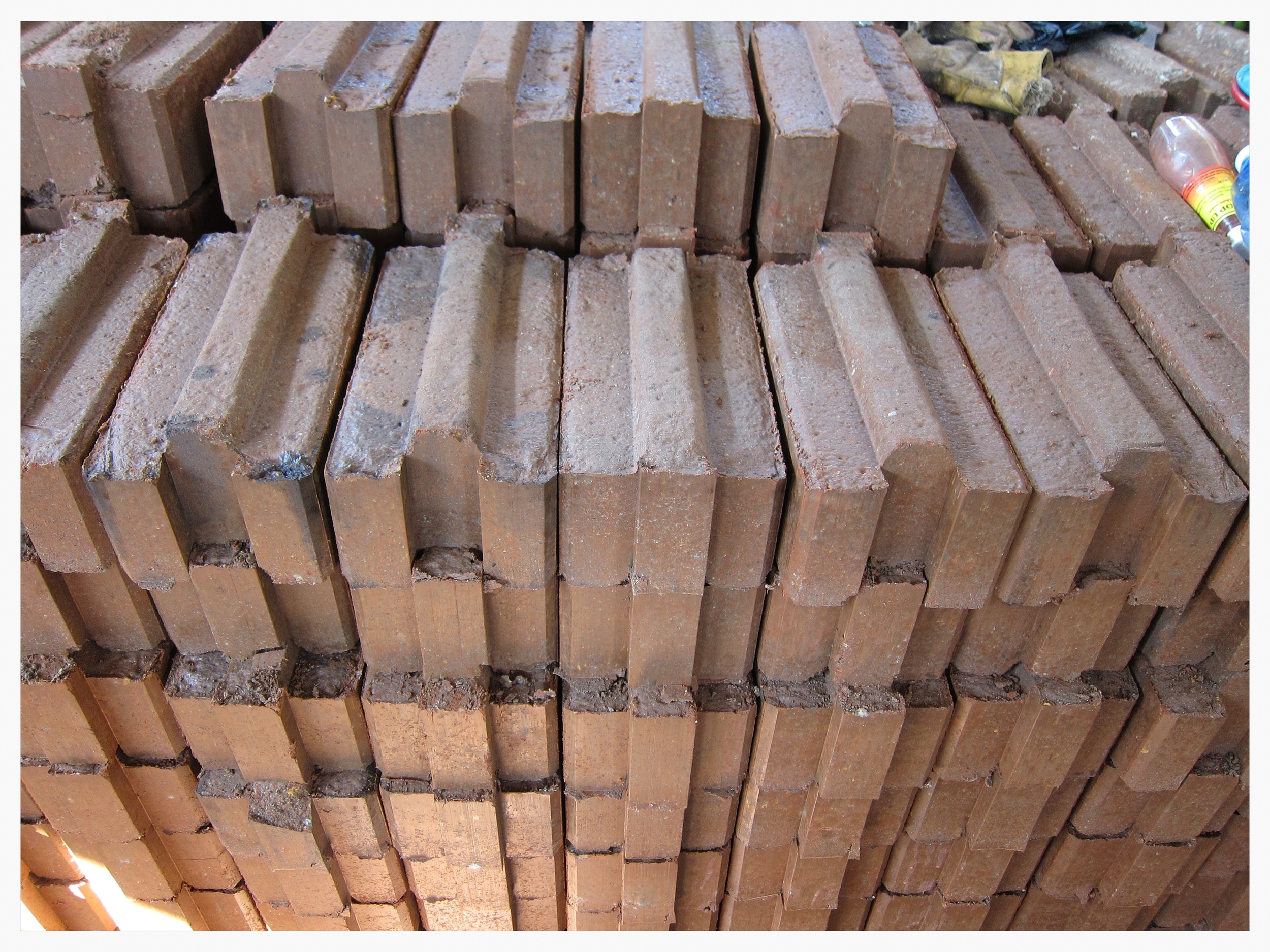 Interlocking Stabilized Soil Blocks are created using local soil combined with basic materials. They are compressed together in a brick press, and then cured for 30 days, rather than fired, saving the cost and toil of gathering firewood.