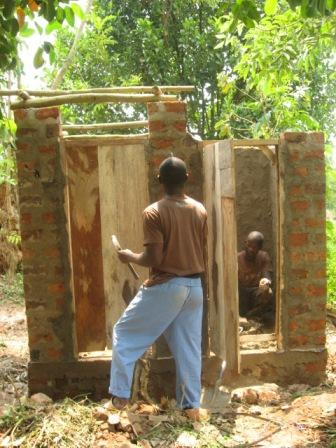 Francis Lubega and his apprentice work on the forms for the roof for his neighbor's new toilet.