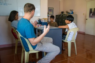 Jason Carpenter teaches on Jesus' feeding of the multitudes out of John at a local center for youth, while a friend translates.