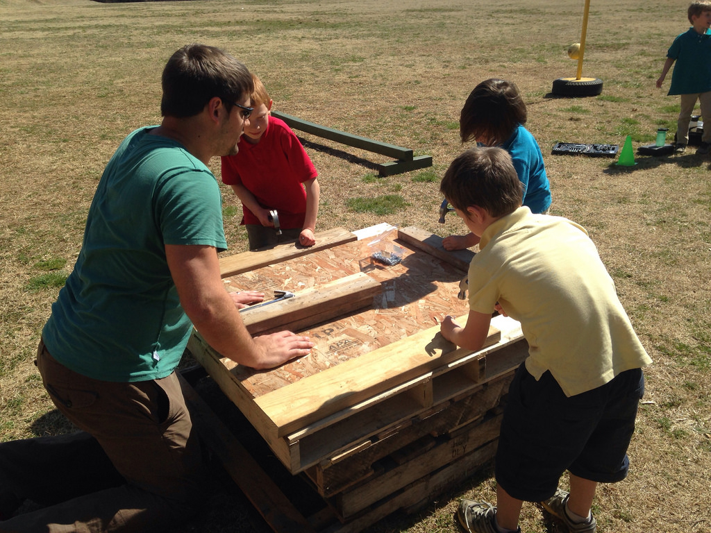 Olson reviews students' hammering skills by creating a relay. The class consists of learning both basic concepts of building as well as actually learning hands-on skills that allow them to implement the concepts in action.