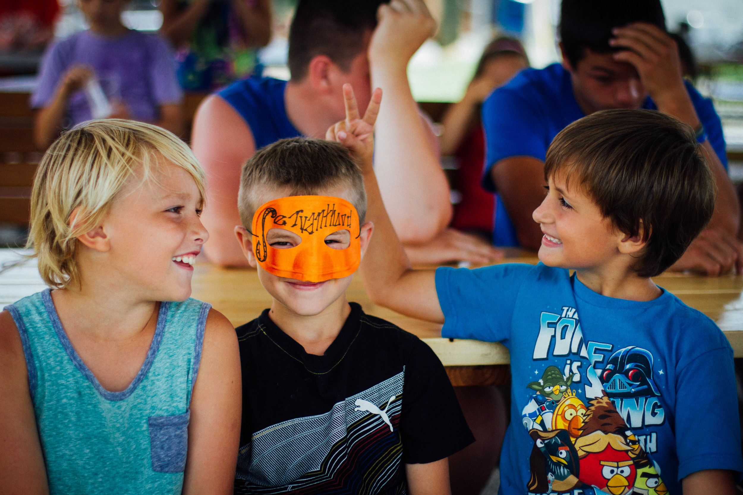 "Elijah Galford, Eved Roufs, and Elijah Smith enjoy lunch at the picnic tables that the boys helped build. Eved dons a ""superhero"" mask that reads ""servanthood""–the most heroic of all traits, and also, the meaning of his name (Eved means ""servant"" in Hebrew). Eved received the mask after displaying servanthood to other campers and counselors throughout the week."