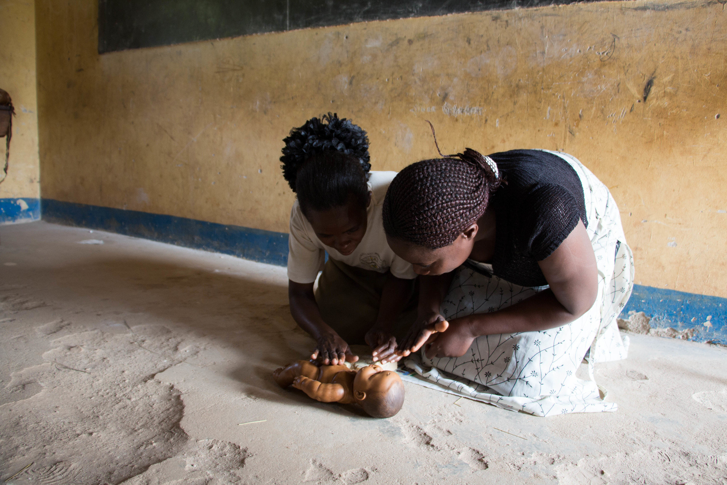 Teachers in Miller's class practice their new skills on infant models. In Uganda where emergency care is scarce, serious accidents typically end in death. Knowing what to do in emergency situations can significantly change people's outcomes.