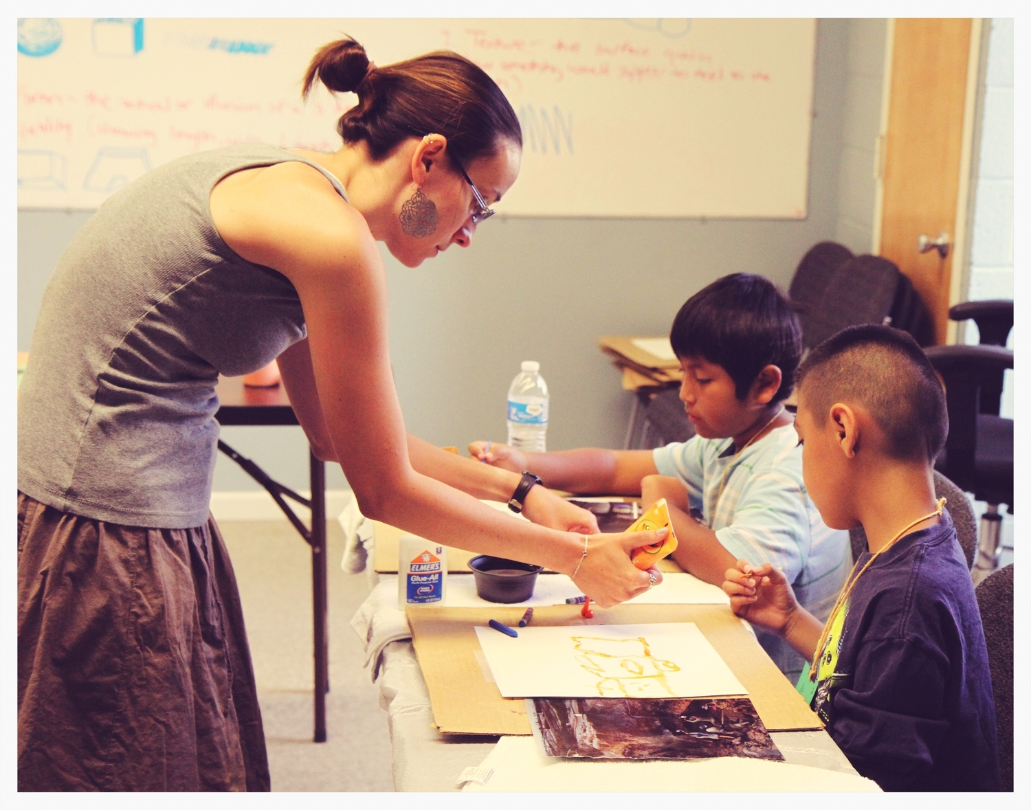 Summer Intern Stephany Dailey helps enable children to express their creative abilities through an art project.