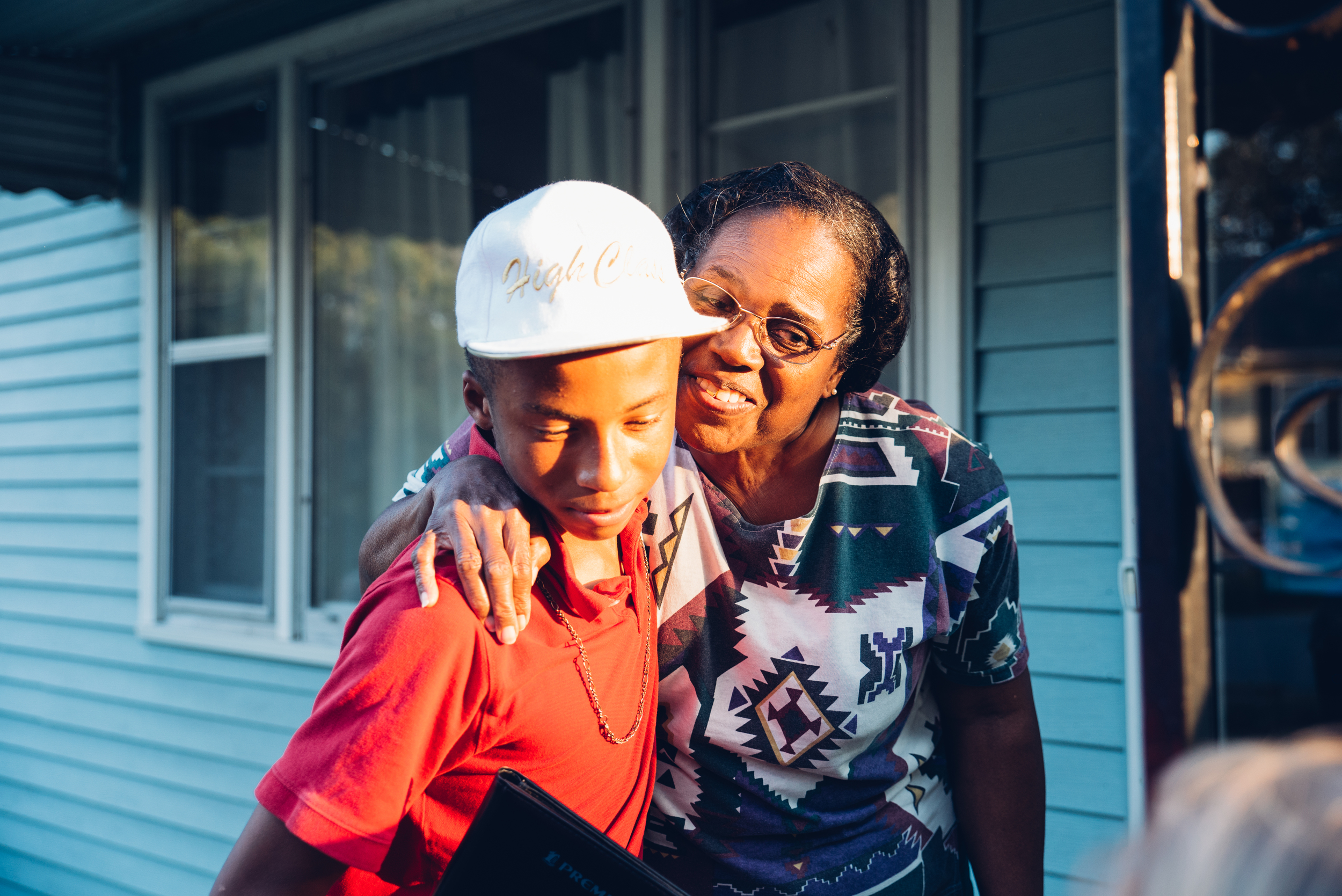 Mrs. Hampton gives Javias a hug after he delivers fresh turnip greens to her door. The experience was impactful for the youth and elderly alike. One student remarked that she was reminded of her own grandmother and aspired to spend more time with her.