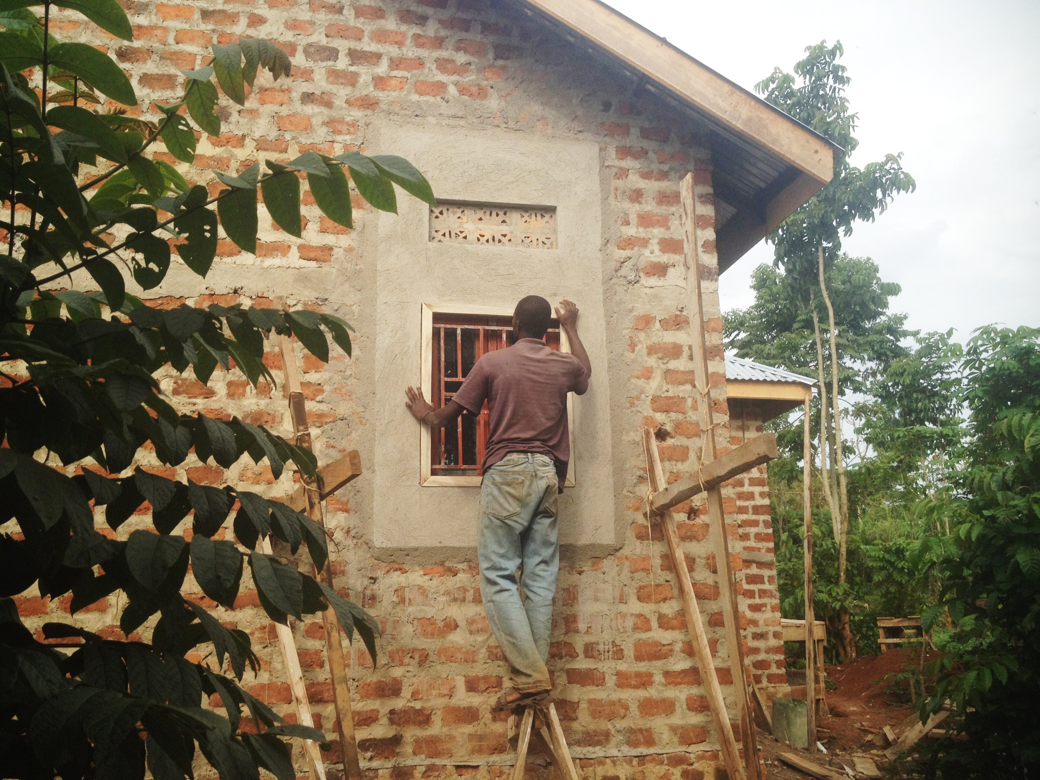 Cooperative and friend of Peter's, Francis Lubega, skilled mason and builder, has been the foreman for Peter's home, and all structures on our property. His apprentice, Tom, is finishing the plaster on Peter's house.