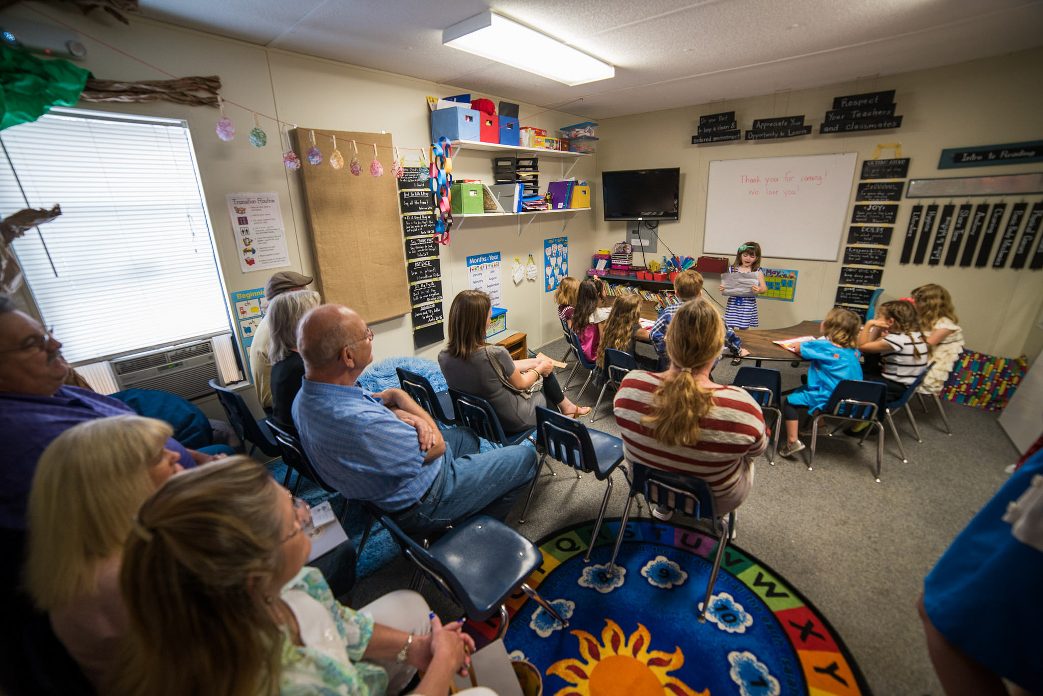 """Norman Cox sits in on his daughter Adia's kindergarten class, alongside other grandparents. For """"sharing class,"""" students shared a story they had written, while being mindful of good eye contact, posture, and volume."""