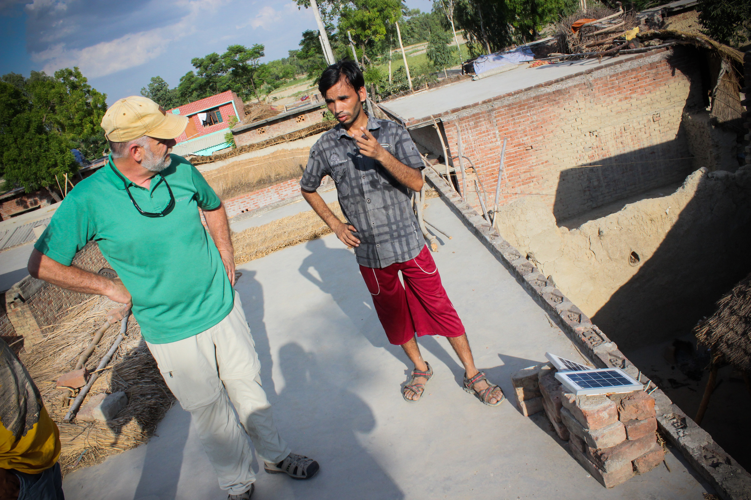 Santosh, our contact in the village, shows Scott Sherrod the solar system sold to a family, on the roof of their home.