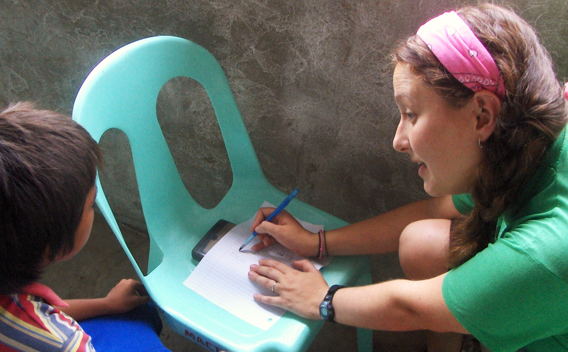 Candace Galford helping a young boy with reading in the Lapu Lapu City dumpsite. The boy's parents work at the dumpsite, scavenging through trash to recycle for income--sadly, a livelihood for many people in the Philippines.