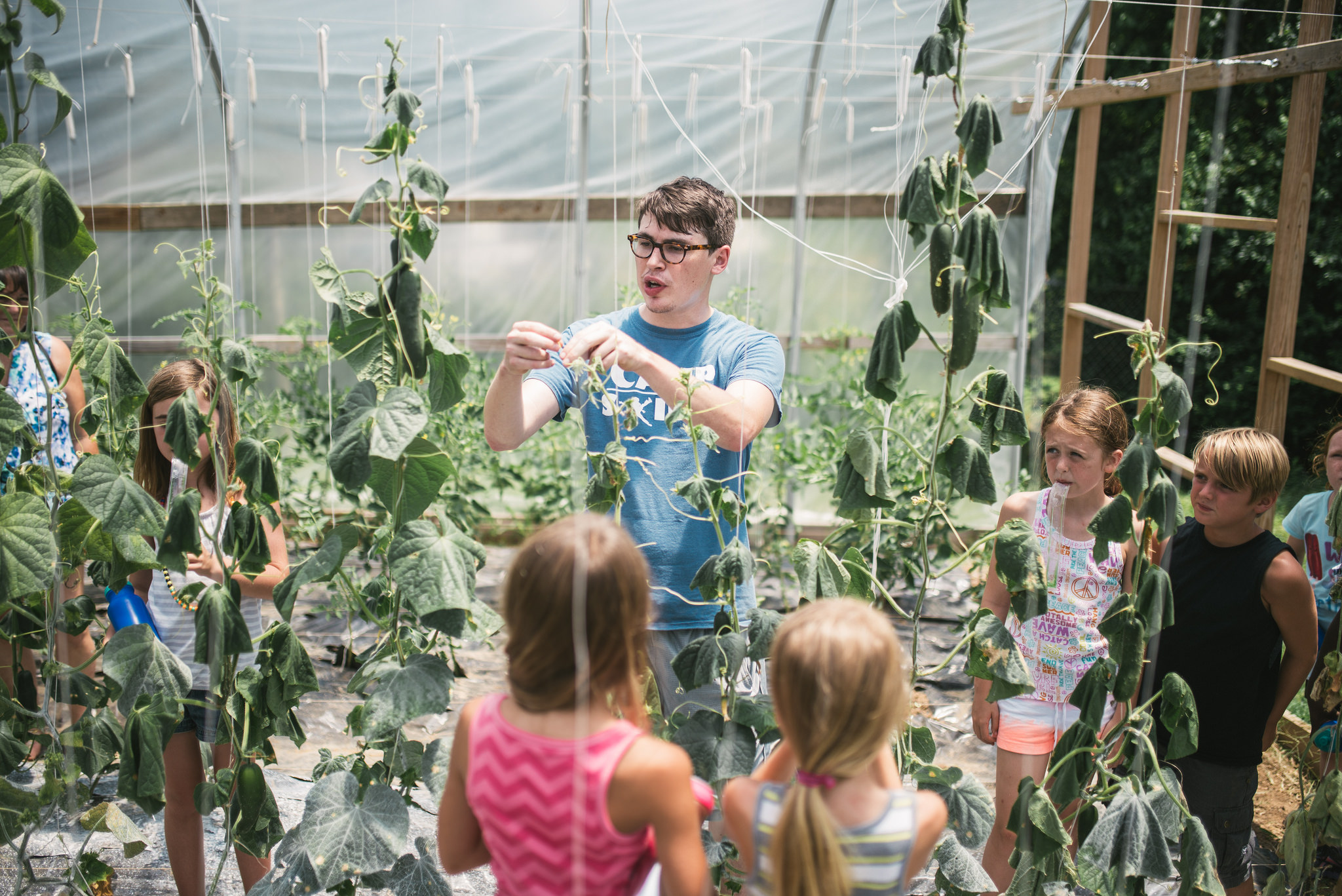 Bryan Sanders, Camp Skillz counselor and consistent community garden volunteer, explains pole beans to campers who get to work in the garden throughout the summer.