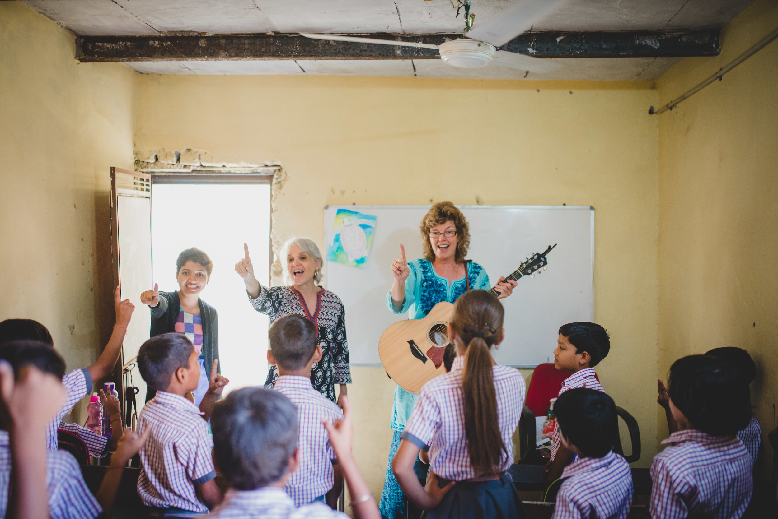 Linda Jobe (right) leads the kids in a song with Rosemary Sherrod, team facilitator, and Mahima, teacher at Aquatic Public School. Linda utilized skills she's gained over many years of leading worship and teaching children. The kids were delighted to learn new songs and motions and Linda was thankful to meet the students her daughter, Kelly, has been teaching for the past month.