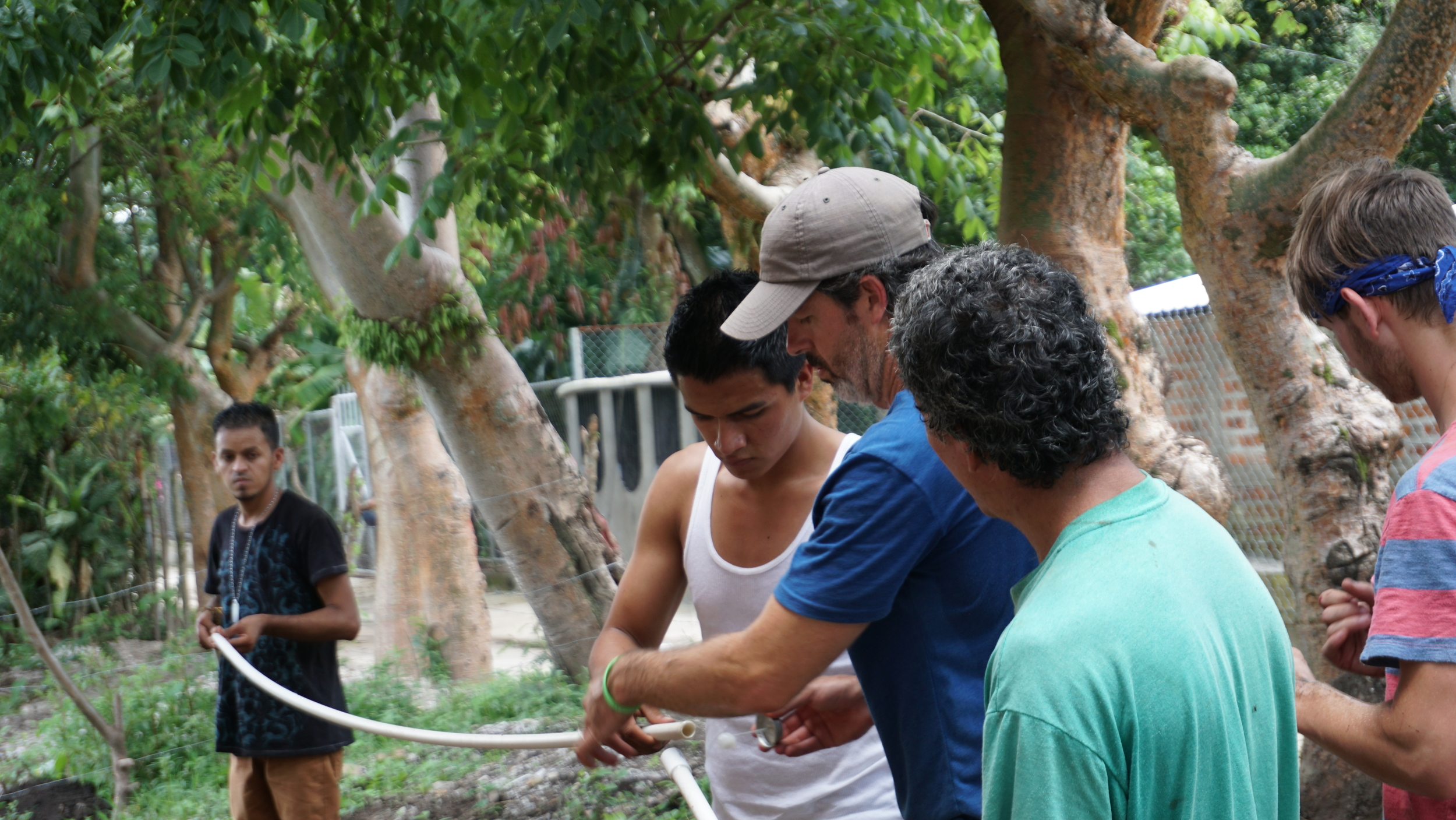 Billy Fly (blue shirt) works with Salvadoran youth to help connect the water line that will run to Noe's (green shirt) house to give him running water.