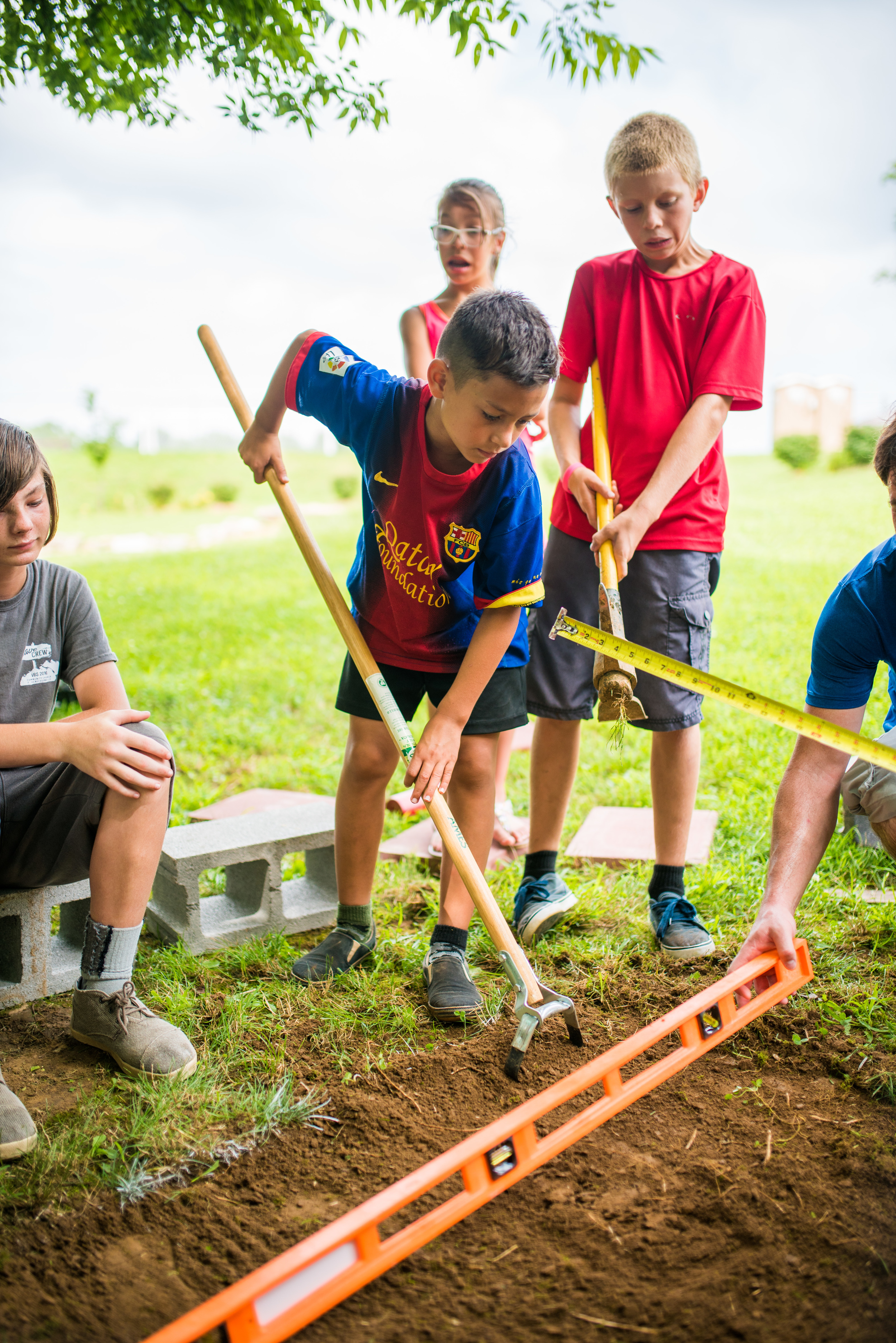 The property at our Old Hickory site is always subject to the educational endeavors of our youth. Justice Garner and Jones Warren work to level off a section of land for the new block built fire pit. The land is to be used, and in this case it was to teach simple masonry skills for the development of practical wisdom for our campers. That's real dirt, real blocks, real tools, and they are really doing all the work to create.