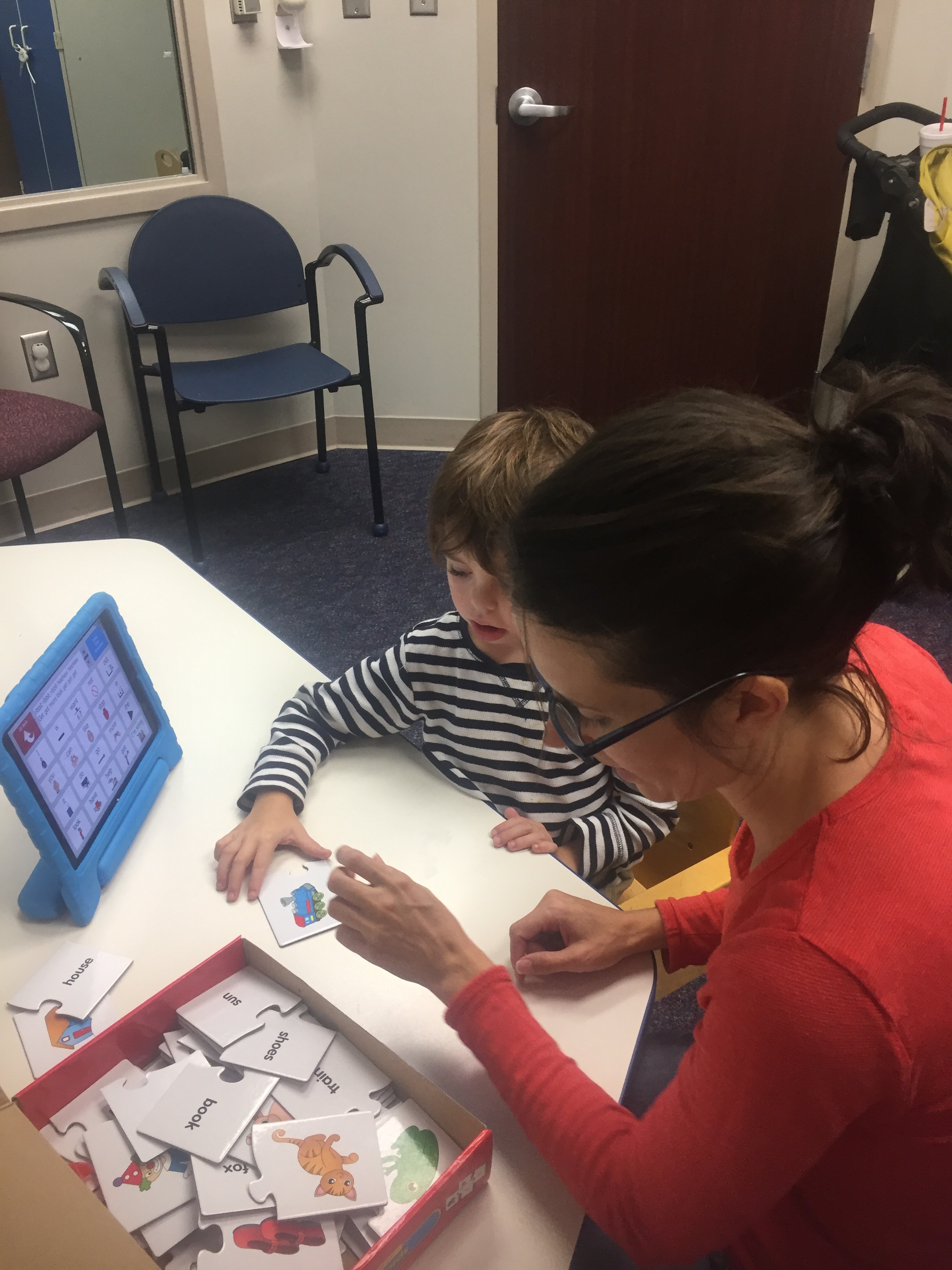 Michelle at Speech Therapy with Levi where he is learning to use alternative means of communication.