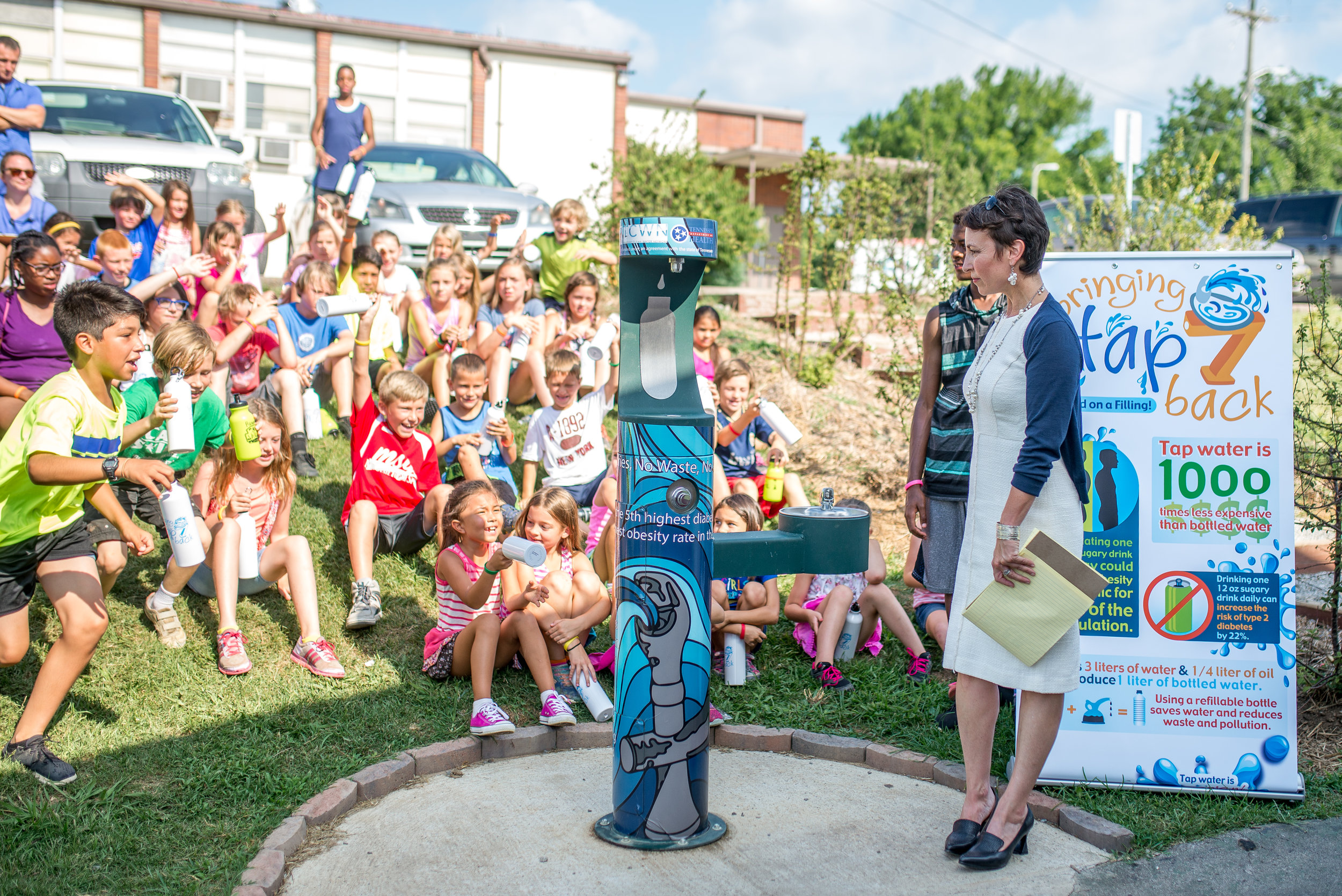 """The Tennessee Clean Water Network gifted us two water fountains to our headquarters where we daily host young people who need refreshing water. Pictured here, participants at Camp Skillz eagerly await their first opportunity to use the new outdoor fountain just outside our community center at the ribbon cutting ceremony where the TCWN program director was interviewed for the local news. Kids from the neighborhood were very grateful, asking us over and over again, """" Is this for us? """""""