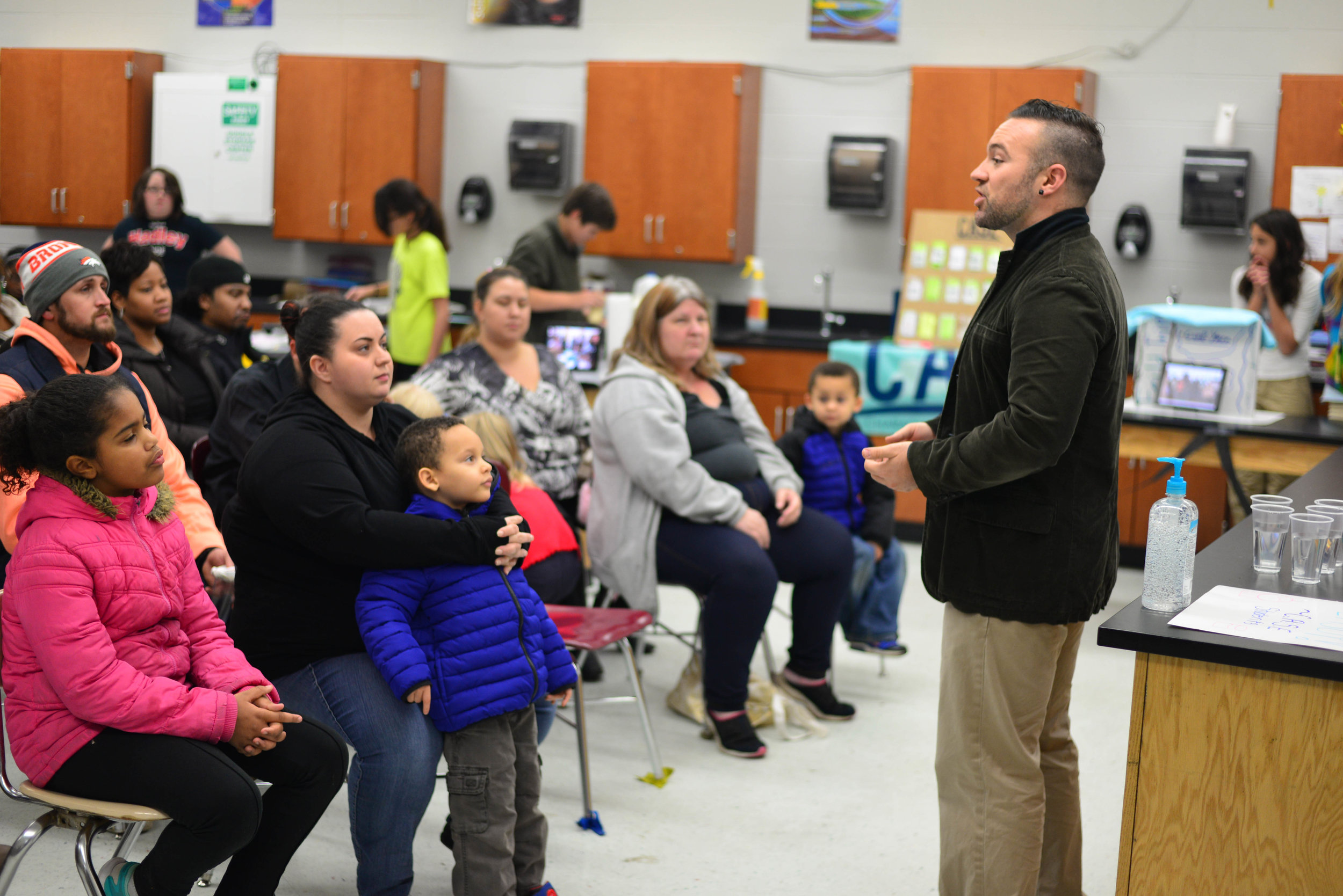 Dupont Hadley Site Coordinator Craig Duffy speaks with parents of C.A.S.E. students at the ShowCASE, where students are able to put on display the skills they have learned over the course of the semester.