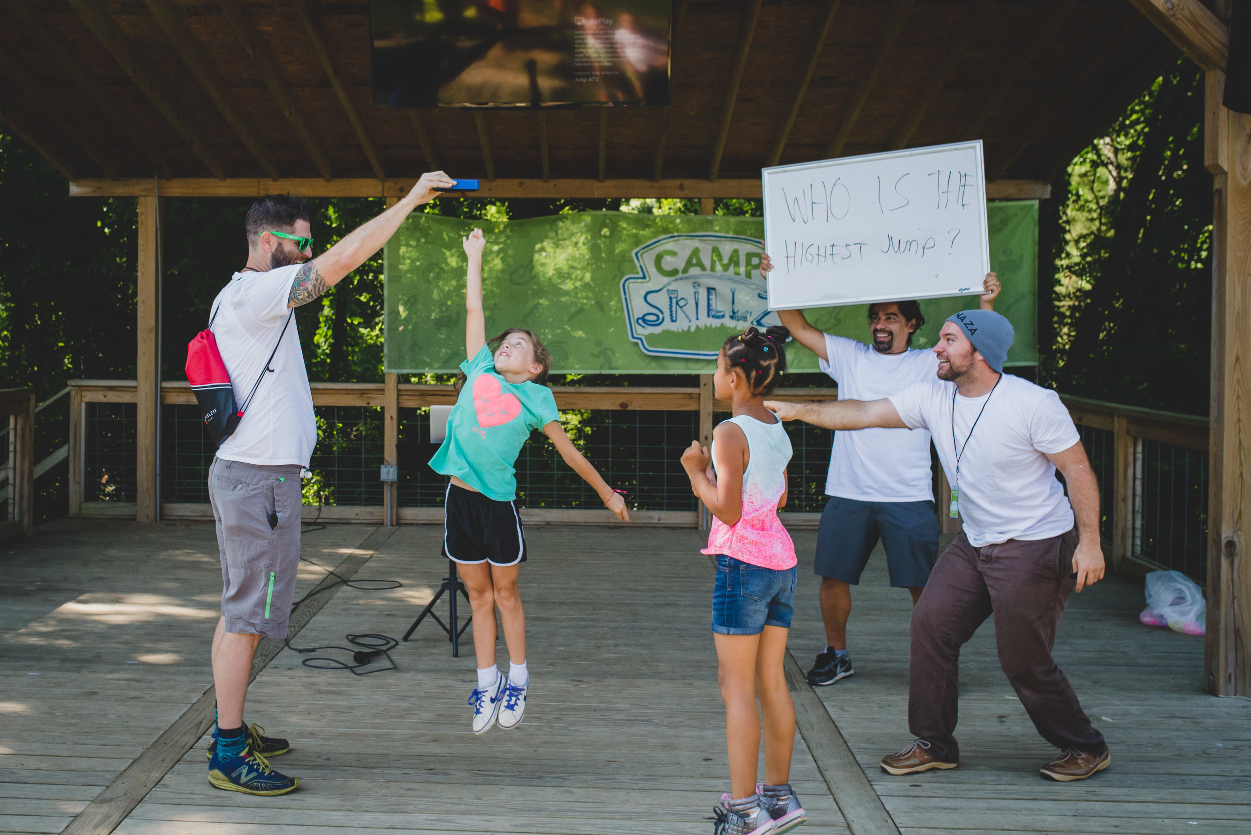 """Academy parent and volunteer extraordinaire John Edmondson helps facilitate camper contests at the Camp Skillz kick off, measuring """"how high,"""" followed by how fast and how strong, from the Camp Skillz motto: Higher, Stronger, Faster."""