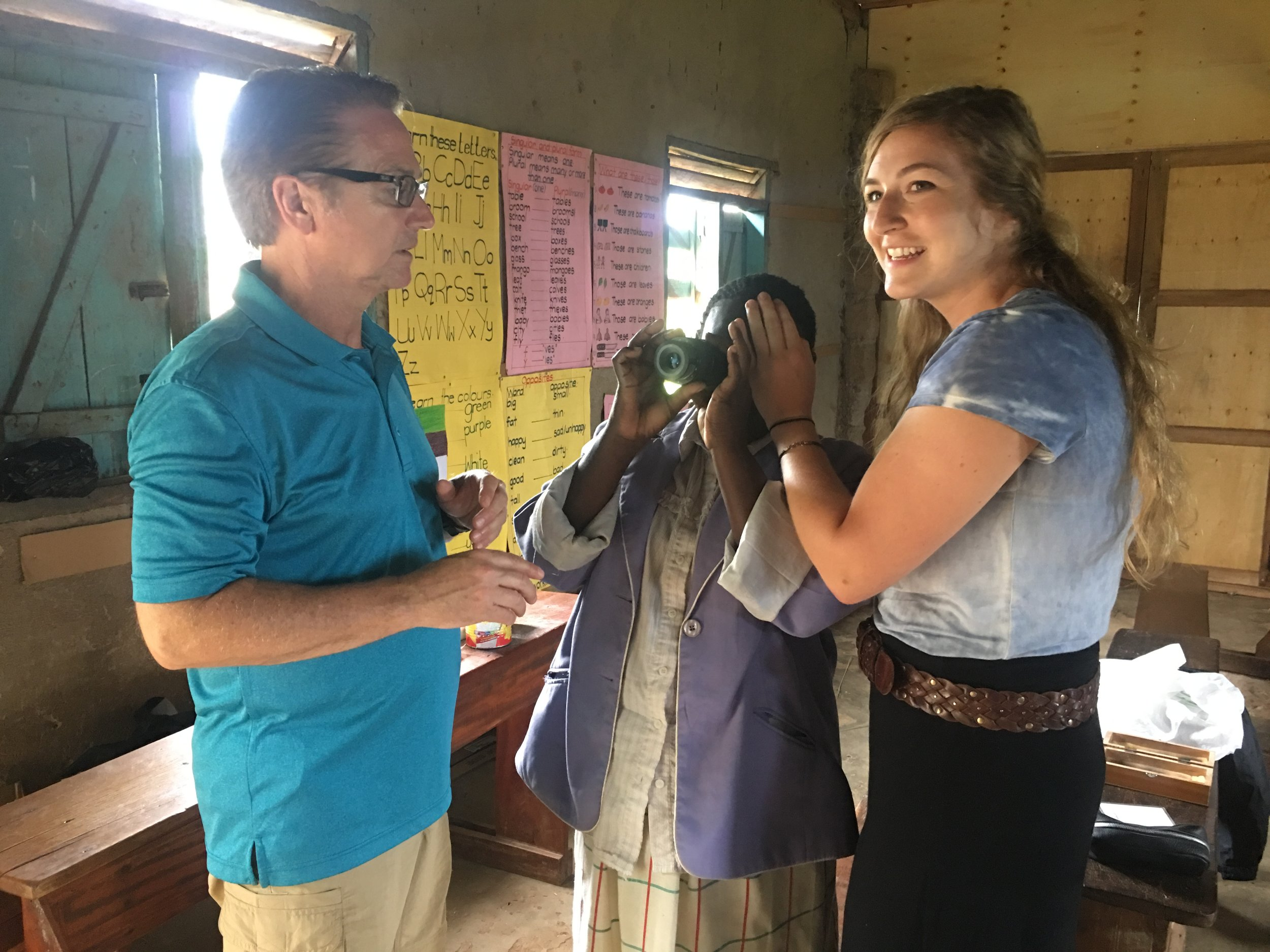 Dr. John Miller and his daughter, Jordan (a member of the G.O.D. East Africa team) conduct an exam on a teacher using a focometer (a device created specifically for third world environments).