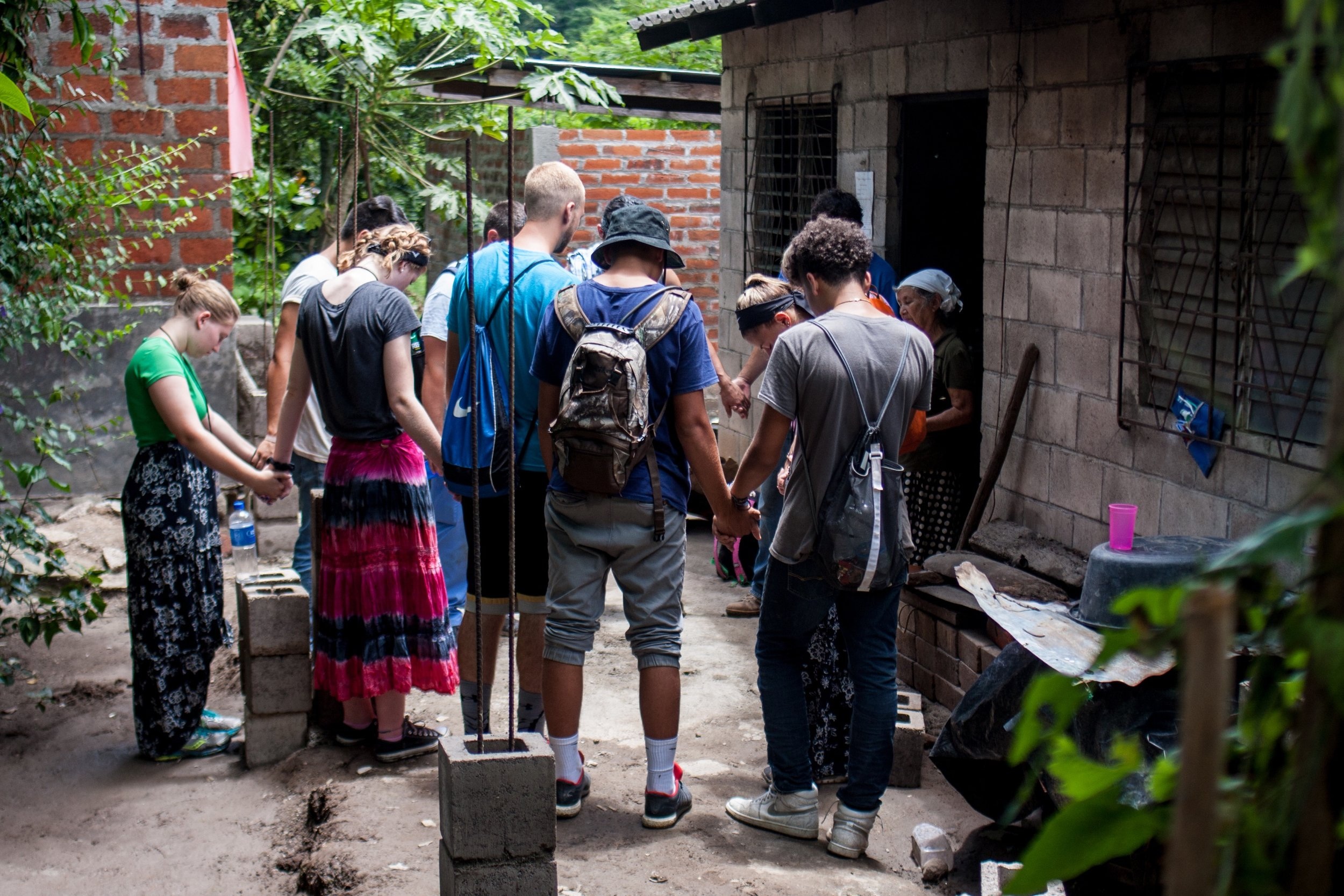 This group prays for Maria, a woman with skin cancer who is awaiting her second surgery, while she cares for two 10-year-old girls. The team repaired her porch roof, which was held up by an unstable tree trunk.