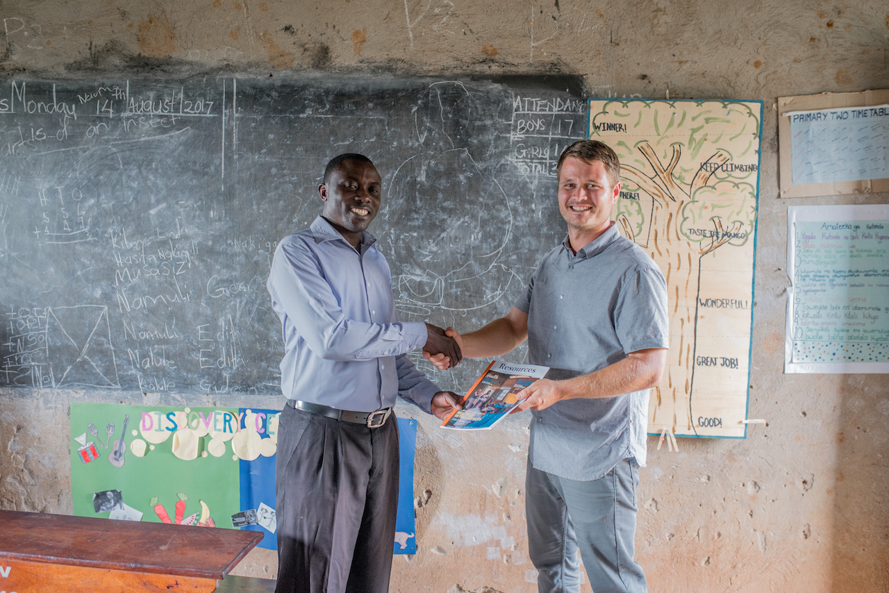 Cameron Kagay, G.O.D. East Africa's Lead Manager, delivers Resources Magazine to the head teacher at St. John's Primary, Lawrence Ssemakula (writer of this article).