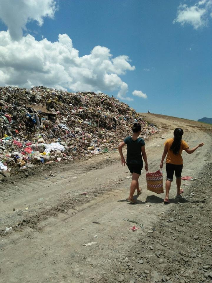 Volunteers from Tahanan carry food to workers at the Tacloban dumpsite.