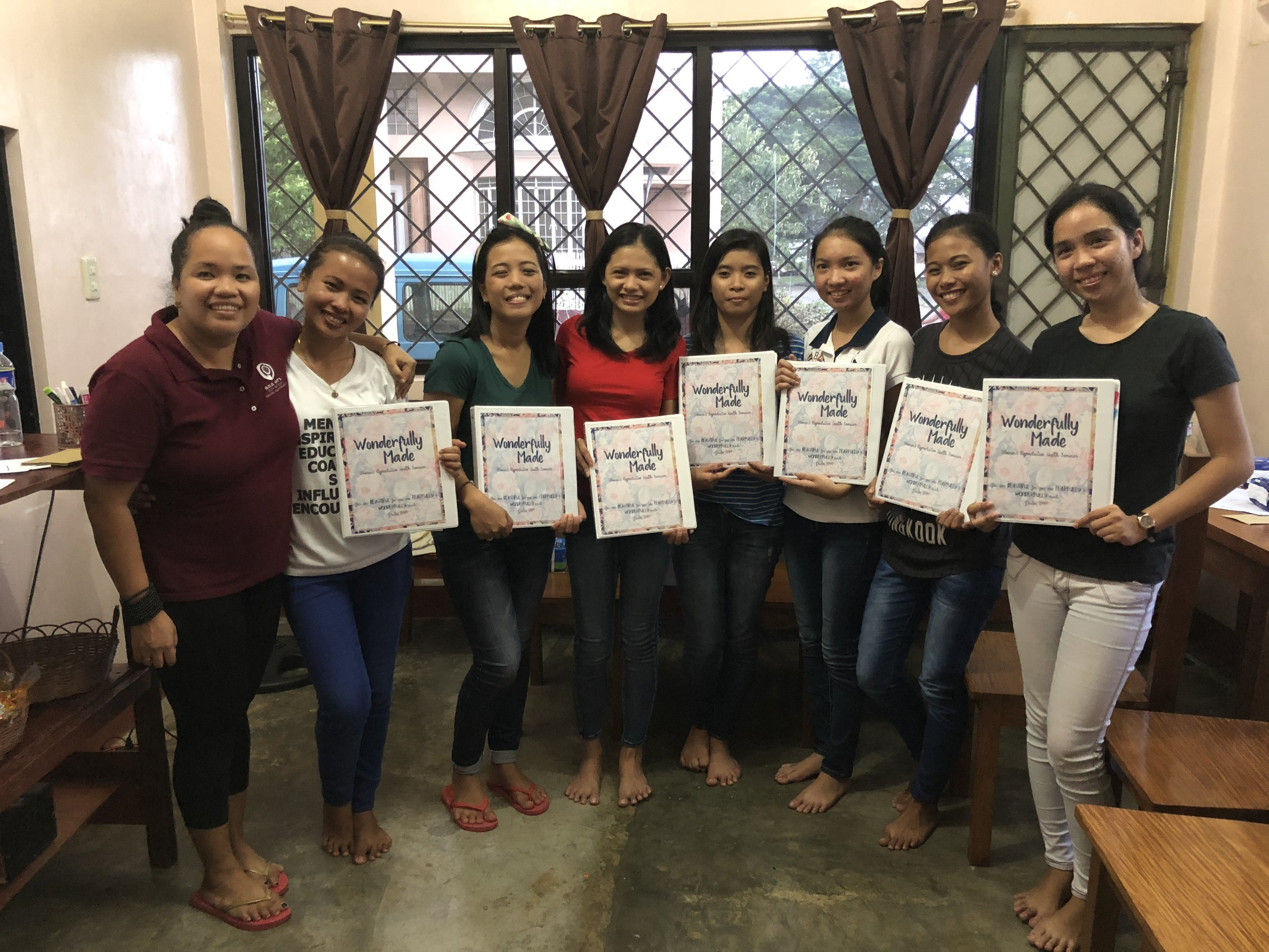 """A group of young ladies hold the curriculum to """"Wonderfully Made"""", a reproductive health seminar that will help these ladies better understand the reproductive process when they move into that season of life."""