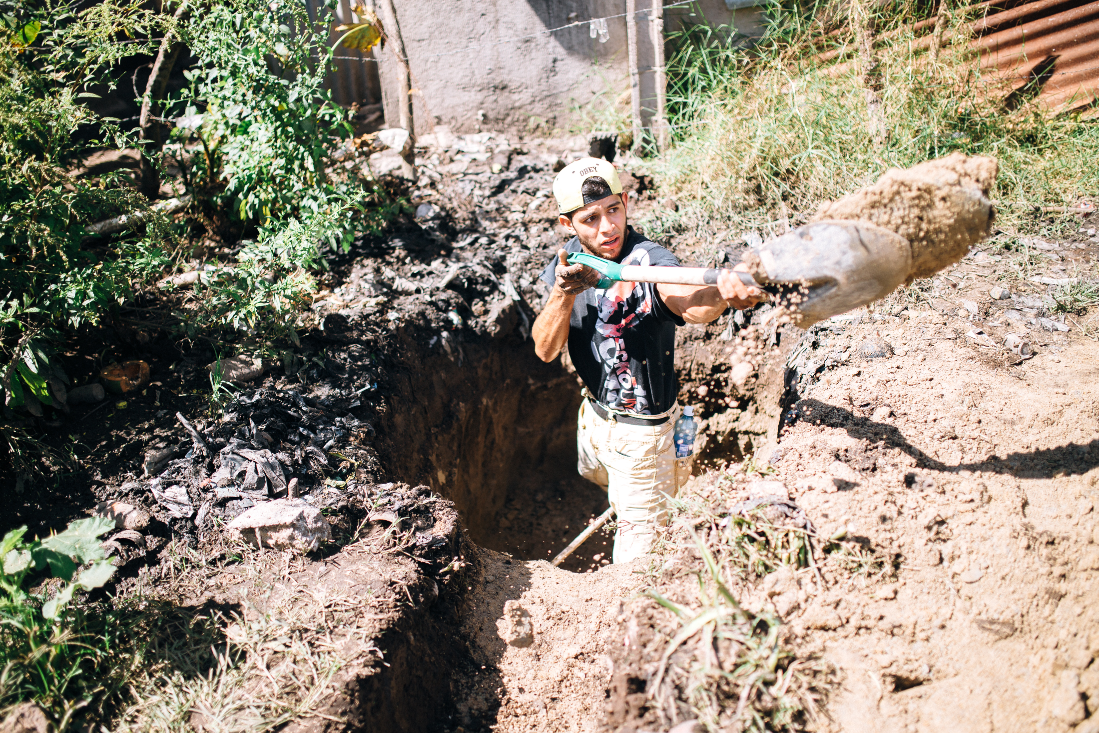 "Working hard is not a new concept to youth in El Salvador, but working hard for a neighbor is. The theme, ""Love God, Love your Neighbor"" was actualized as the youth spent their energy and their time meeting needs for neighbors. Here, Amilcar digs what will become a trench for dirty water, so his neighbor's yard won't flood after every shower."