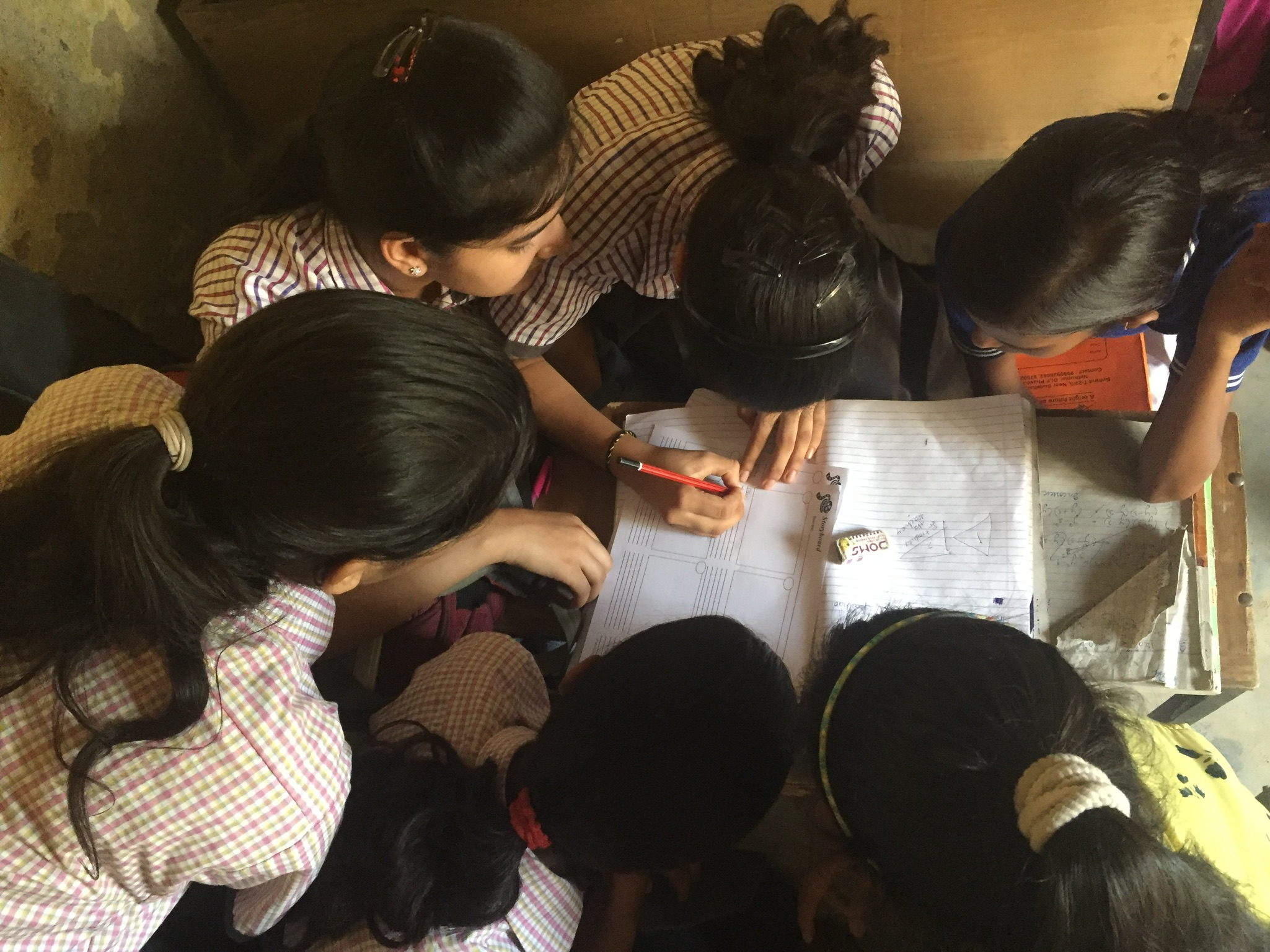 The project incorporated elements of language arts and visual arts, all with a heavy emphasis on cooperation within a team dynamic. Here, girls work together to storyboard a plot and arrange an appropriate length for a children's book.
