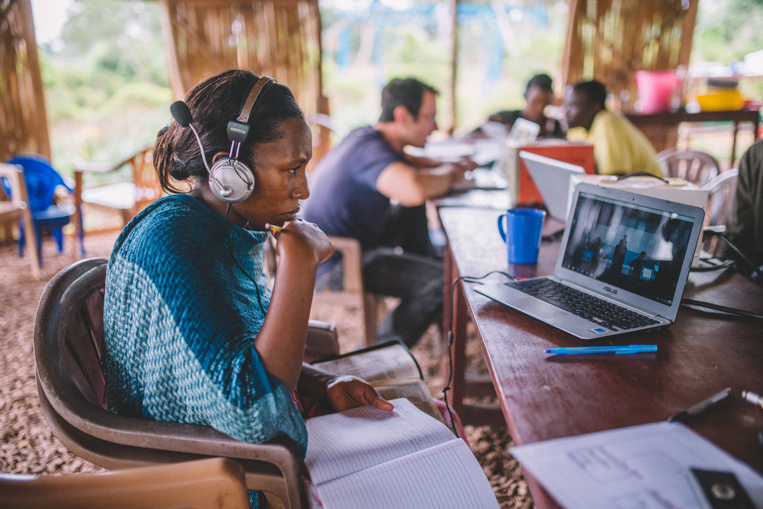 """Annette Nabugo tunes in to her cooperative Bible class """"Biblical Foundations for Ministry,"""" recorded at the Institute for G.O.D. and made available via the internet to her home in rural Uganda. Behind her, Brandon Galford, a Bible teacher, meets with other students to review the material."""