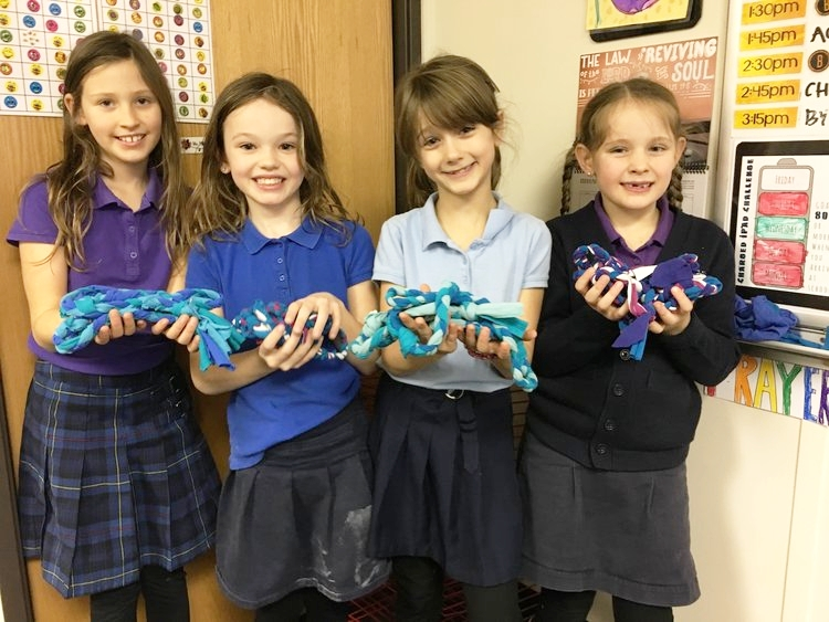 In Ms. Foster's Textiles class, 7-8 year olds read about different types of fabric to determine which would make the best jump ropes, then practiced fine motor skills by cutting and braiding old T-shirts, transforming them into awesome recess toys! Students also learned sewing techniques and made their own pillows.