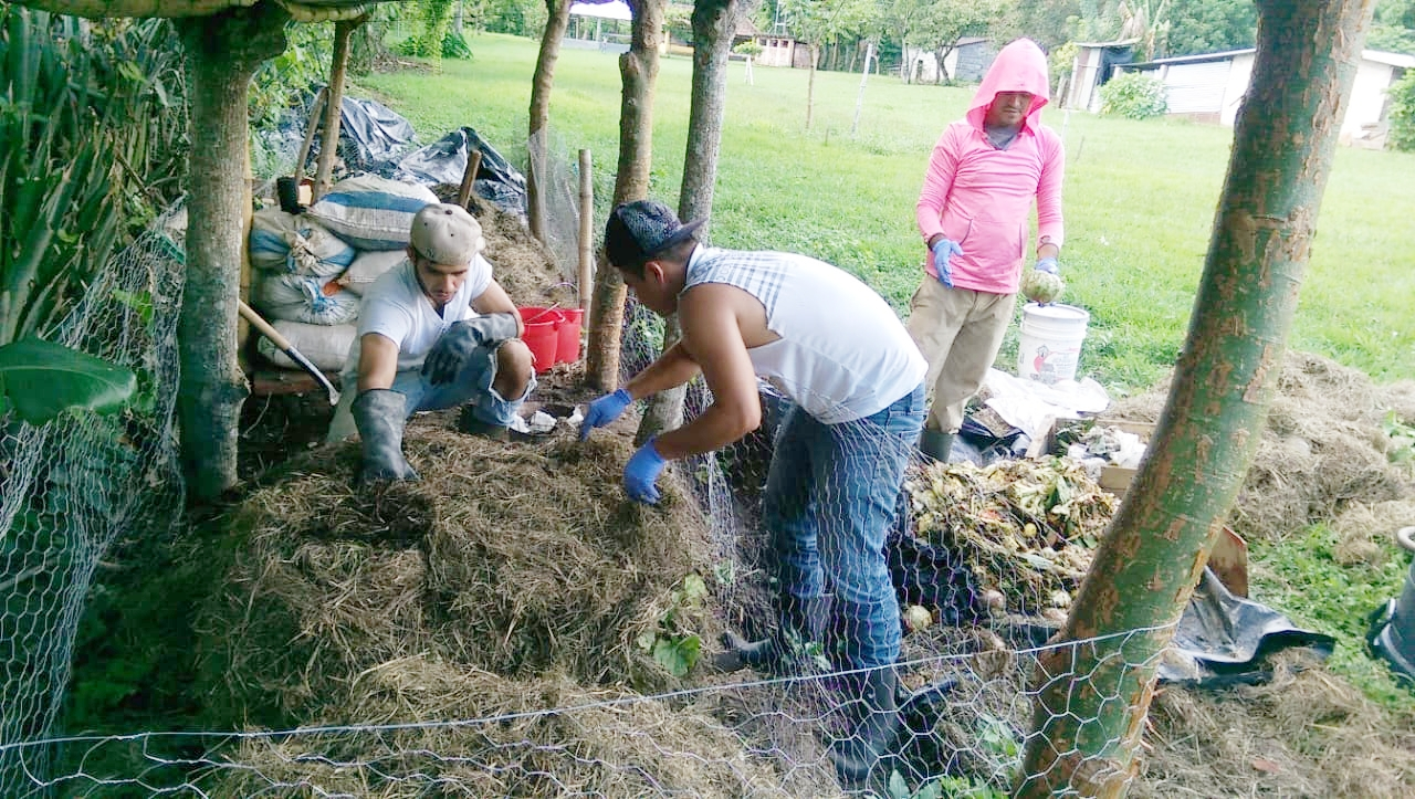 """Interns Miguel, Willian and Amilcar work to """"cook"""" compost to improve the soil of the garden. Composting was not a familiar concept to Antonio at first, but now that the beds have had time to """"cook"""" and he's used the soil to grow food in abundance, he's a firm believer!"""