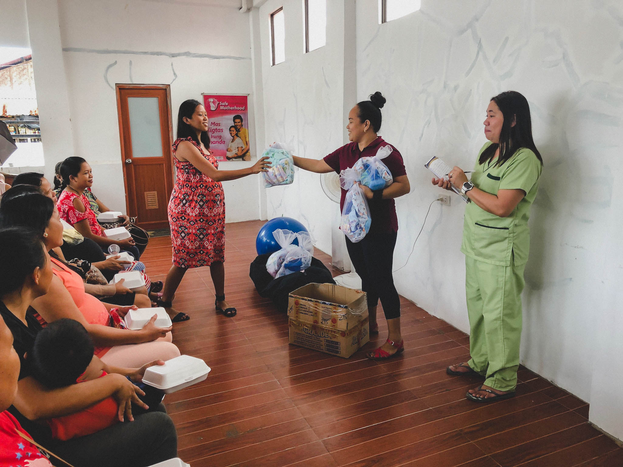 Rina Miller and Nerissa, a midwife at Cumpio Clinic, share necessary supplies with the mothers who attended the conference, helping them to get the start they deserve with adequate supplies.
