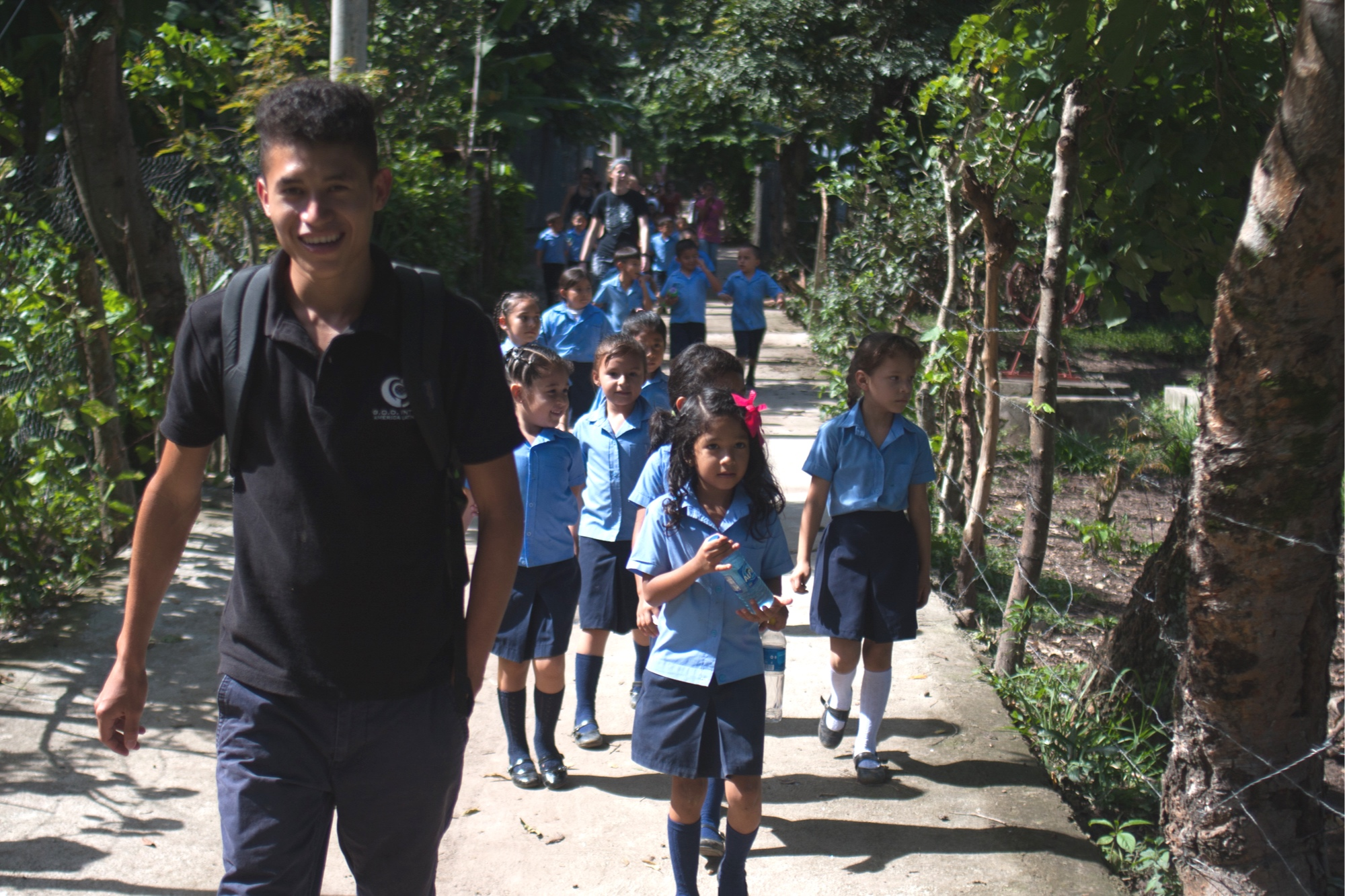Both interns volunteer 8 hours each week at the local school near our Salvadoran campus. Orlando (pictured here walking with a Kinder class) teaches guitar for level 4 using both his growing interest that is being spurred on by this class.