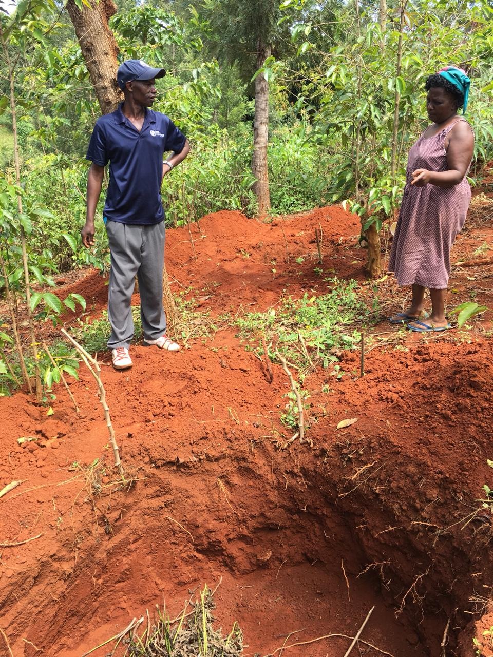 Simon shares with a neighbor the process of adding compost to the pit.