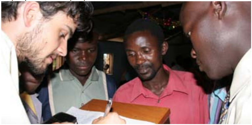 July 5, 2005: Summer Intern Jeff Sherrod writes down a list of the pastors who are without a Bible in their native language. At this conference in Uganda 17 of the 32 pastors and leaders who attended did not have a Bible!