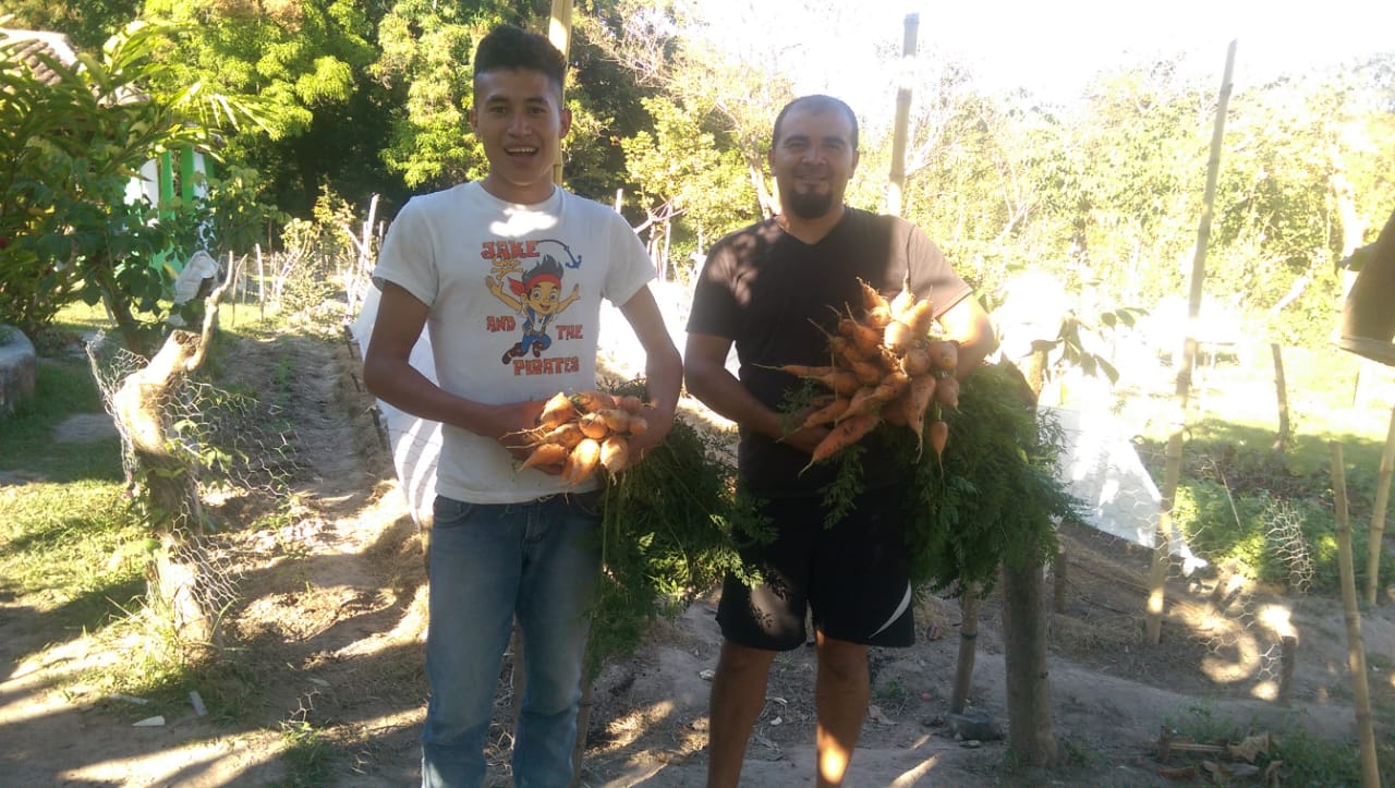Student Intern, Orlando Pineda (left), and Garden Manager Antonio Mejía (right), show off a successful carrot harvest from the campus garden.