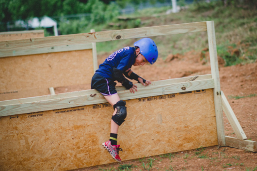 Camper Evan Olascoaga is encouraged to muscle through the obstacles in the mud course in order to develop his sense of grit: having the passion and resolve to complete a goal.
