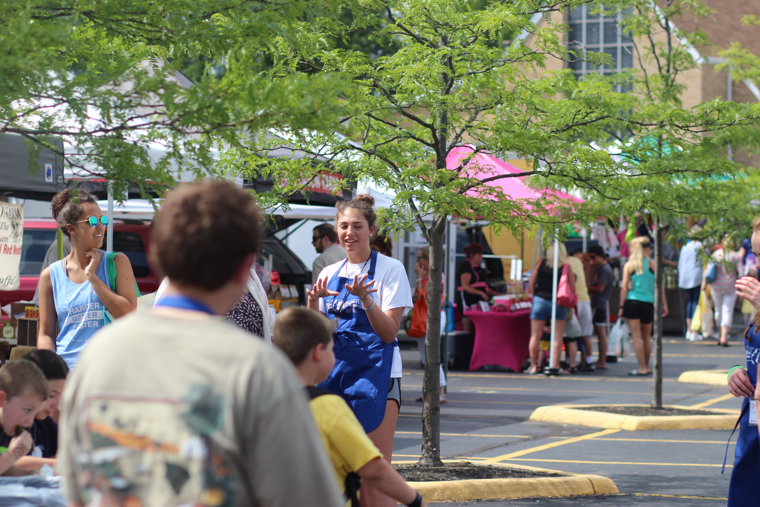 """SLAM participant, Cora, talks to customers about the """"New Neighbors, International Bakers and Makers"""" booth at a local farmer's market and explains how it helps to support refugee women and their families."""