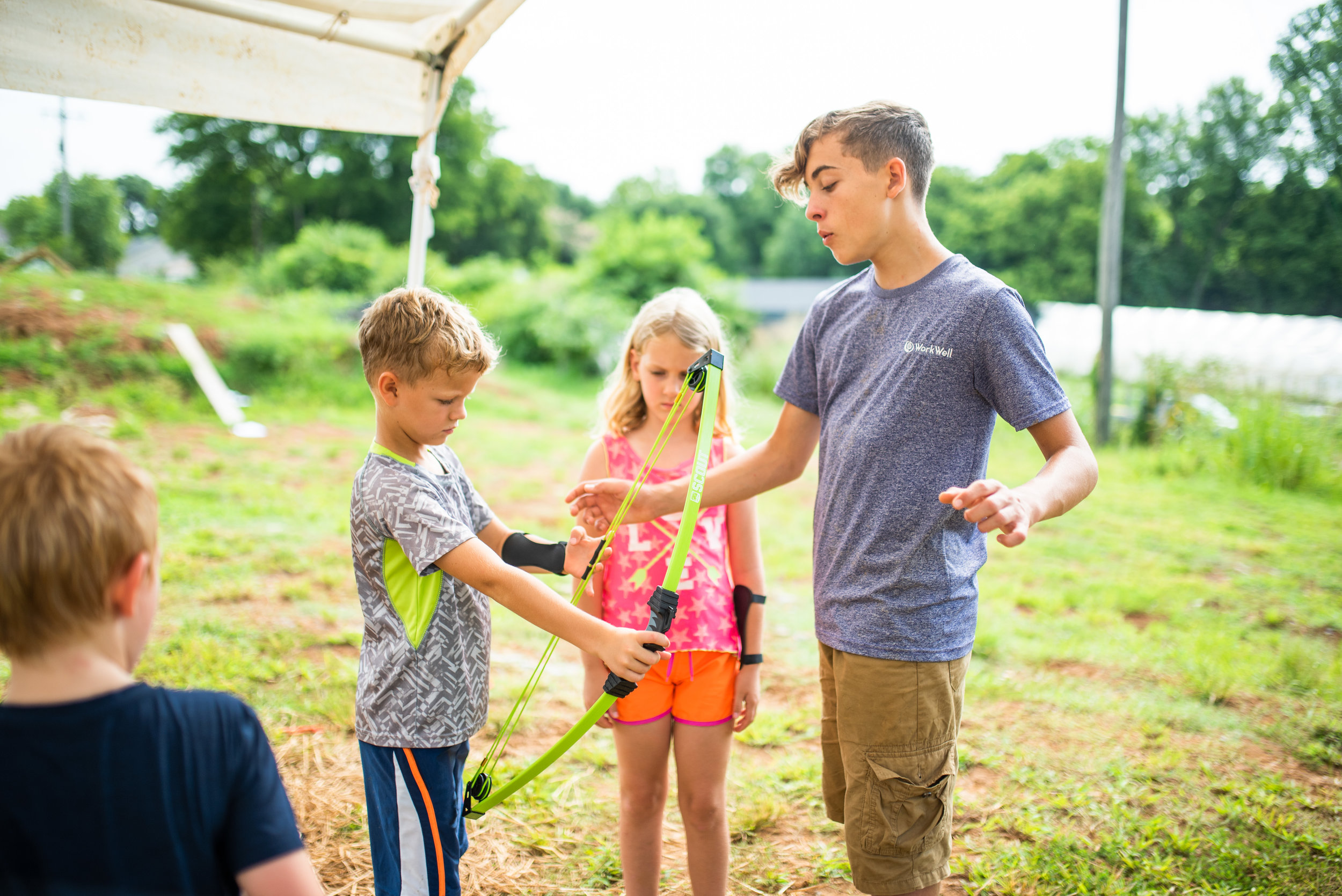 "River Riechert helps campers at Camp Skillz learn how to do archery during their ""Survivor Island"" week."