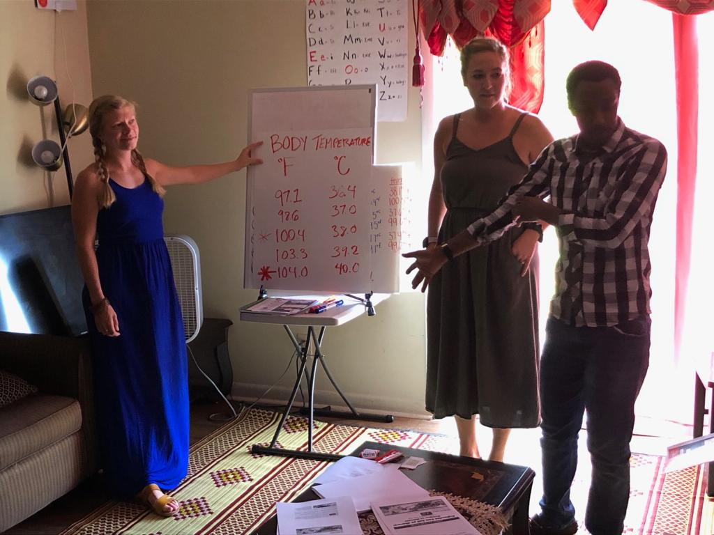 Christina James and Jordan Miller, both medical assistants and members of the G.O.D. East Africa team, teach Congolese refugees how to tell temperature in preparation to read thermometers for the first time.