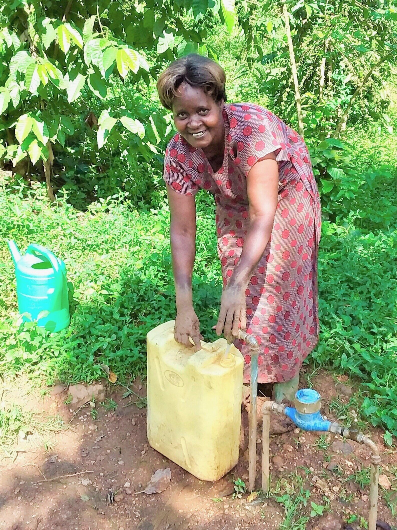 Margaret, Moses' mother, filling a 20 liter jerry can from their water tap near their home.