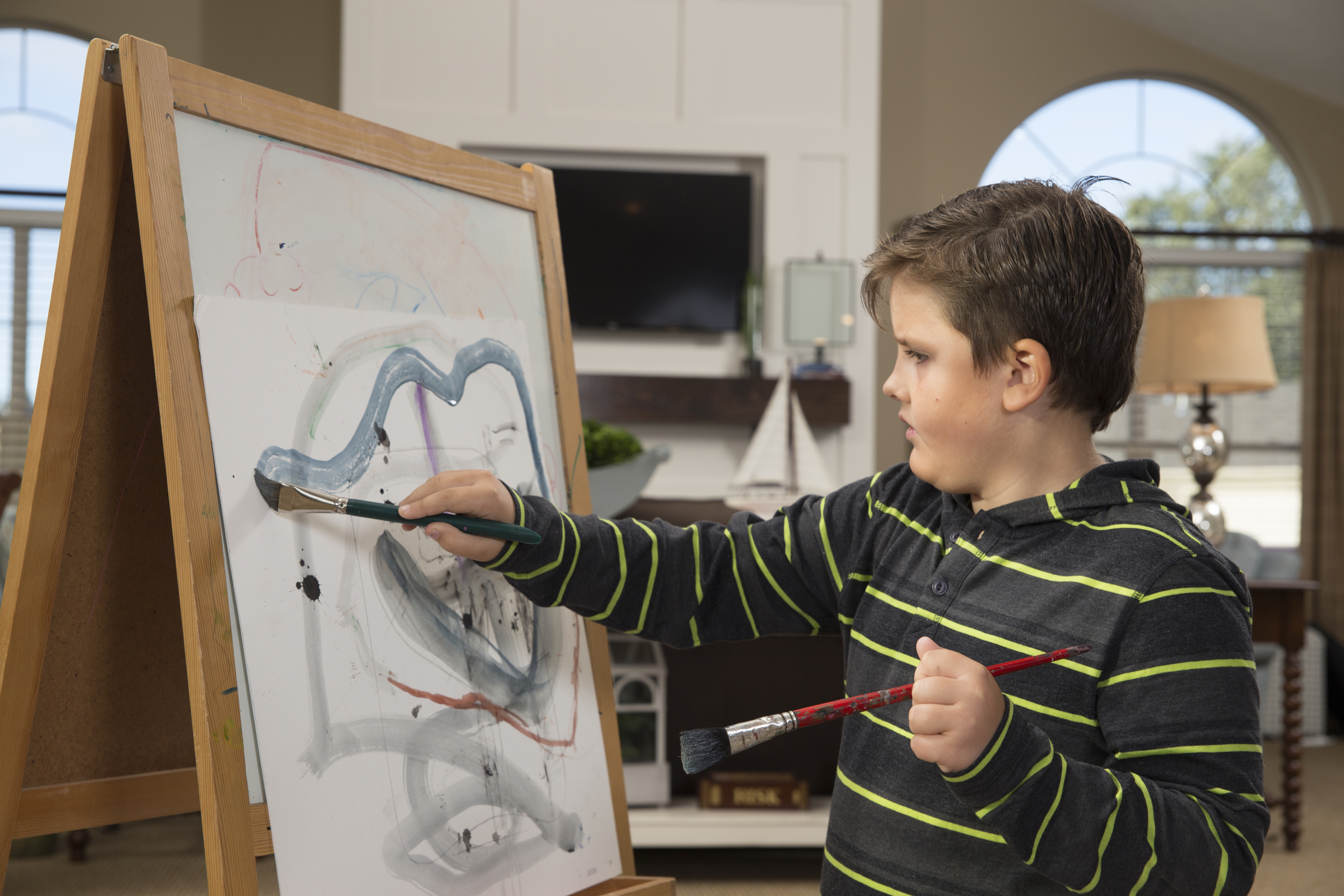 Image of young boy painting in a nice house