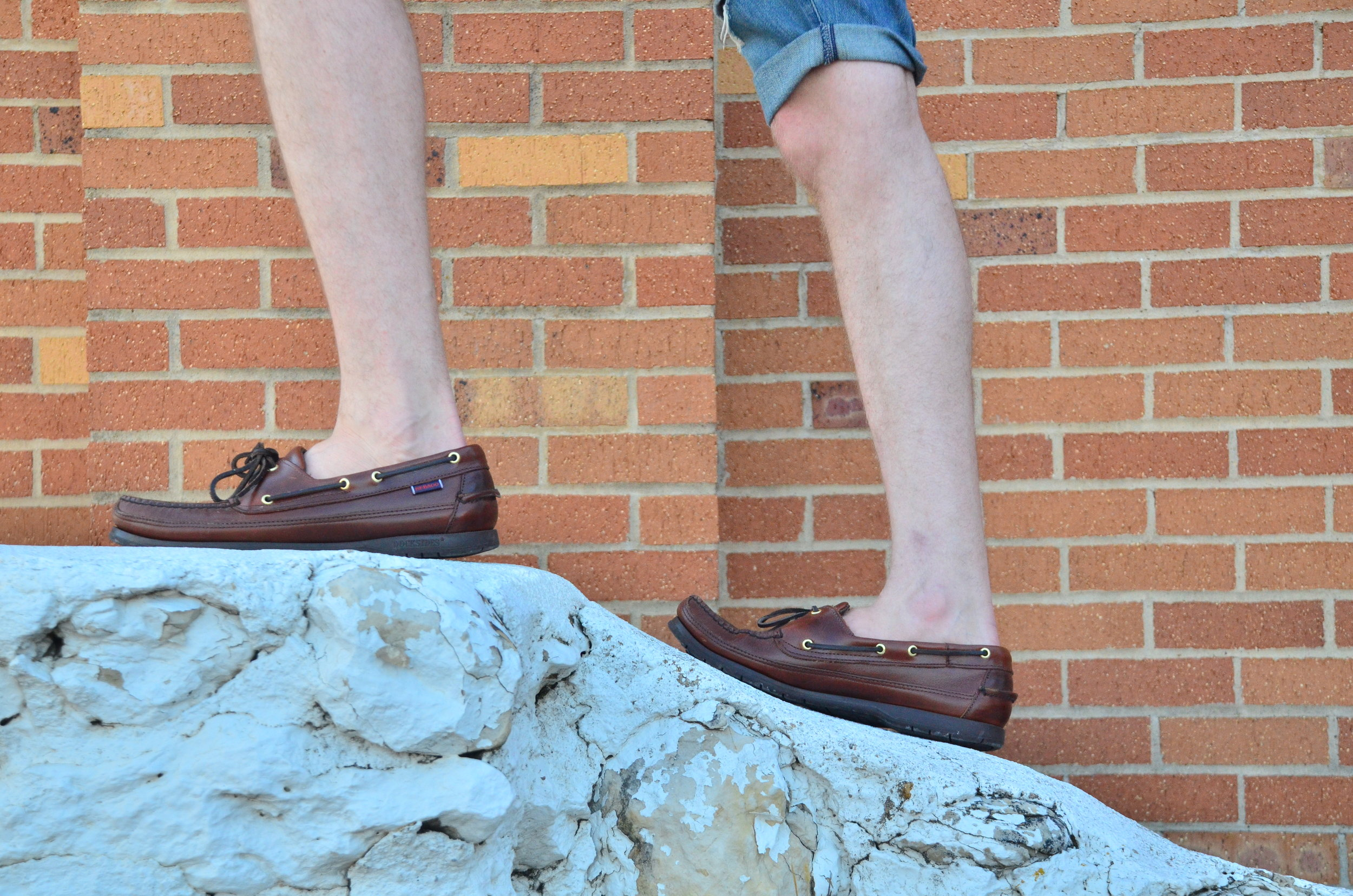 Standing on a curved white wall, wearing Sebago boat shoes