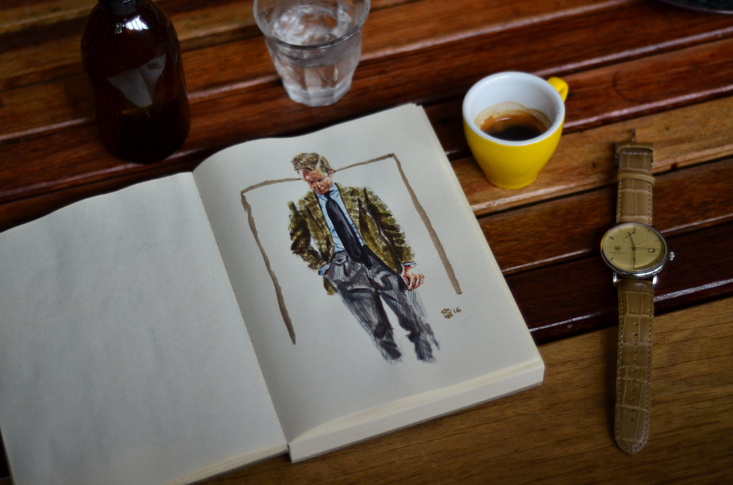 Open sketchbook sitting on table at a cafe with espresso