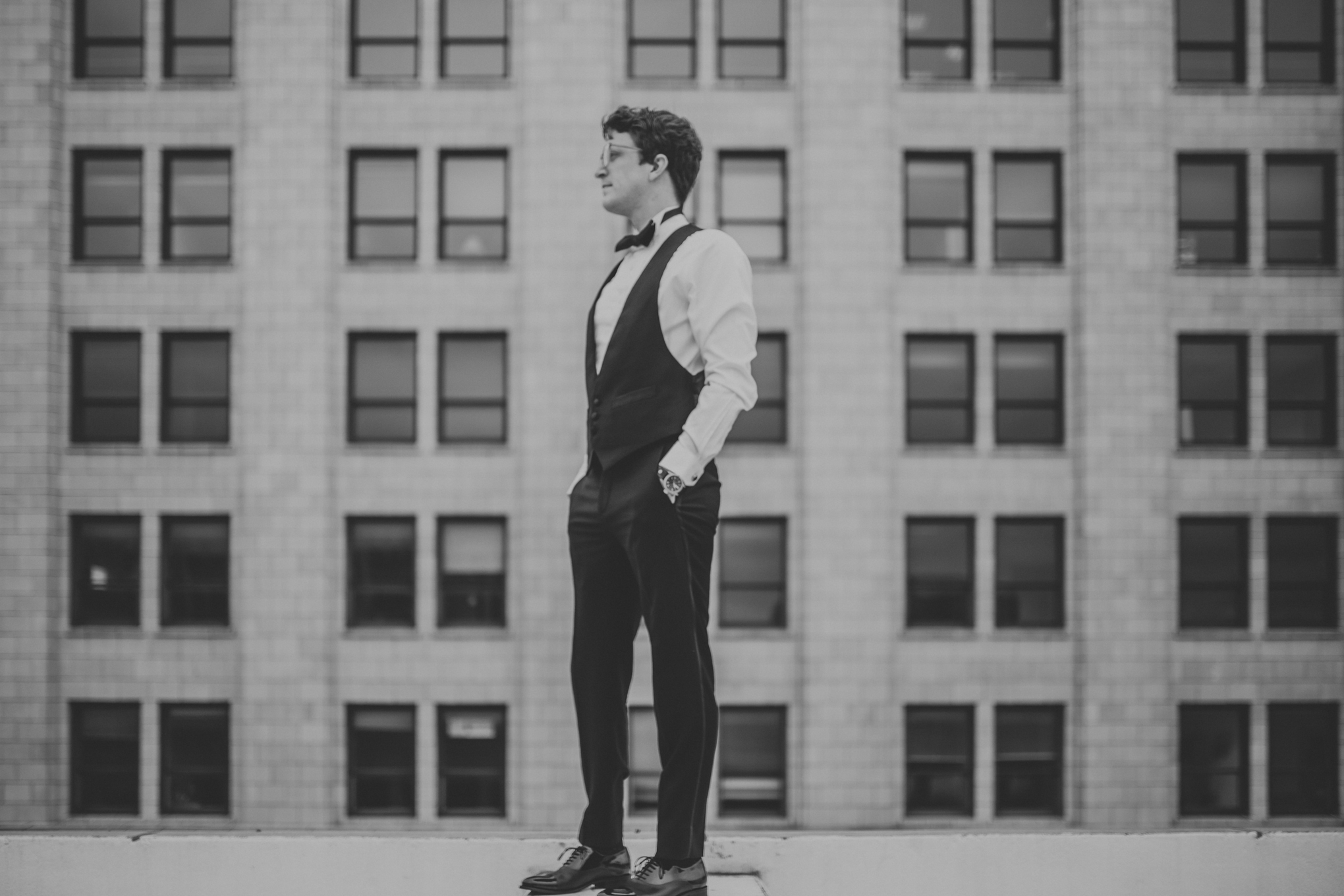 black and white photo of man standing near top of city wearing The Black Tux