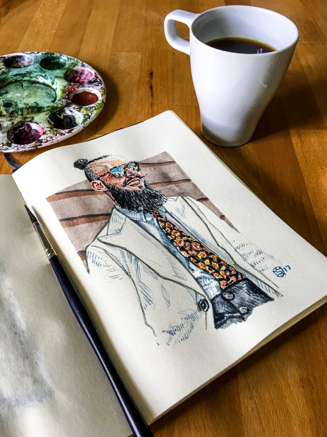 Artur Santos illustrated portrait on a table with coffee