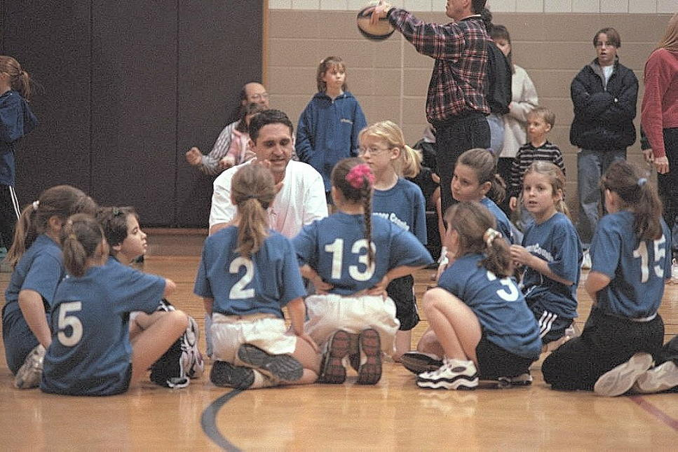 Coach Chris speaks to the Lil' Flames at a game, where seldom was heard a discouraging words.